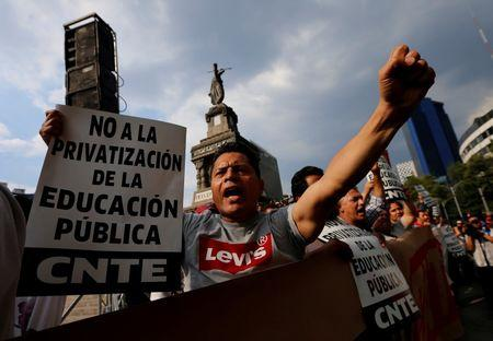 Protesters from the National Coordination of Education Workers (CNTE) teachers' union holds signs in a march against President Enrique Pena Nieto's education reform, along the streets in Mexico City, Mexico June 17, 2016. REUTERS/Henry Romero