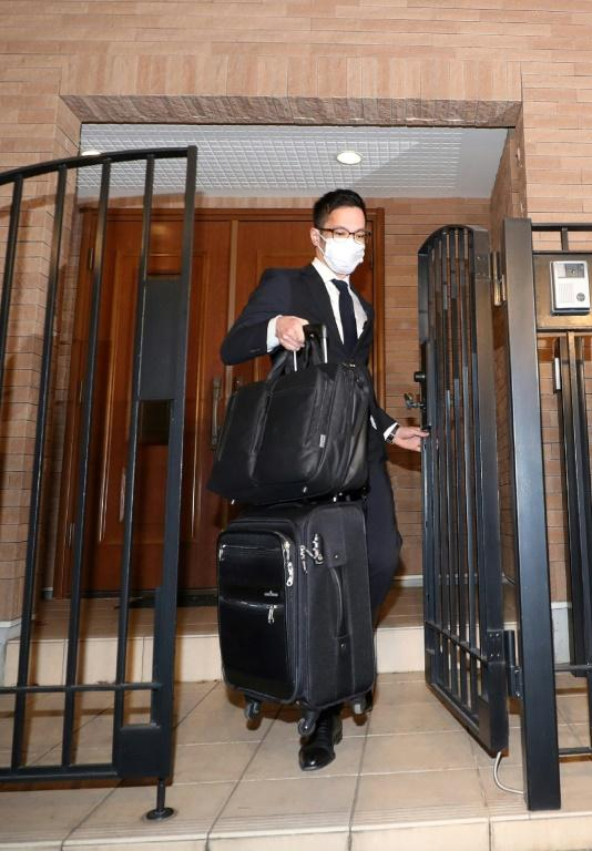 A Japanese prosecutor carries bags from the Tokyo residence of former auto tycoon Carlos Ghosn after Ghosn fled Japan to avoid a trial (AFP Photo/STR)