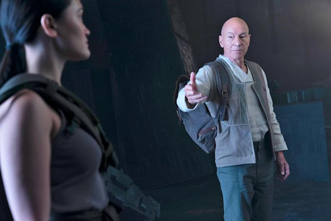 Captain Picard gestures towards someone.