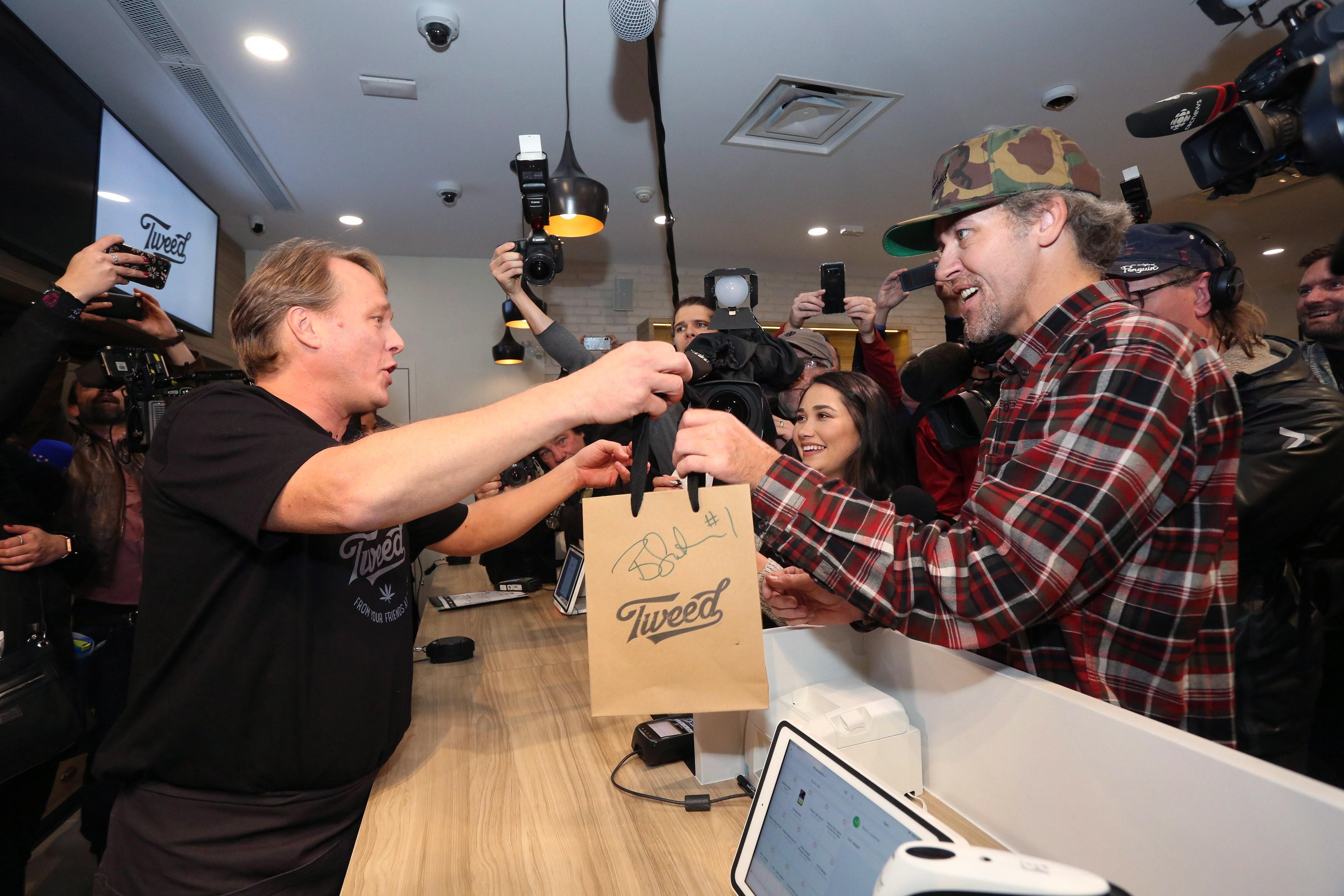 <p>Canopy Growth Corporation CEO Bruce Linton, left to right, passes a bag with the first legal cannabis for recreation use sold in Canada to Nikki Rose and Ian Power at the Tweed shop on Water Street in St. John's N.L. at 12:01 am NDT on Wednesday October 17, 2018.<br>(Photo from Paul Daly, The Canadian Press) </p>