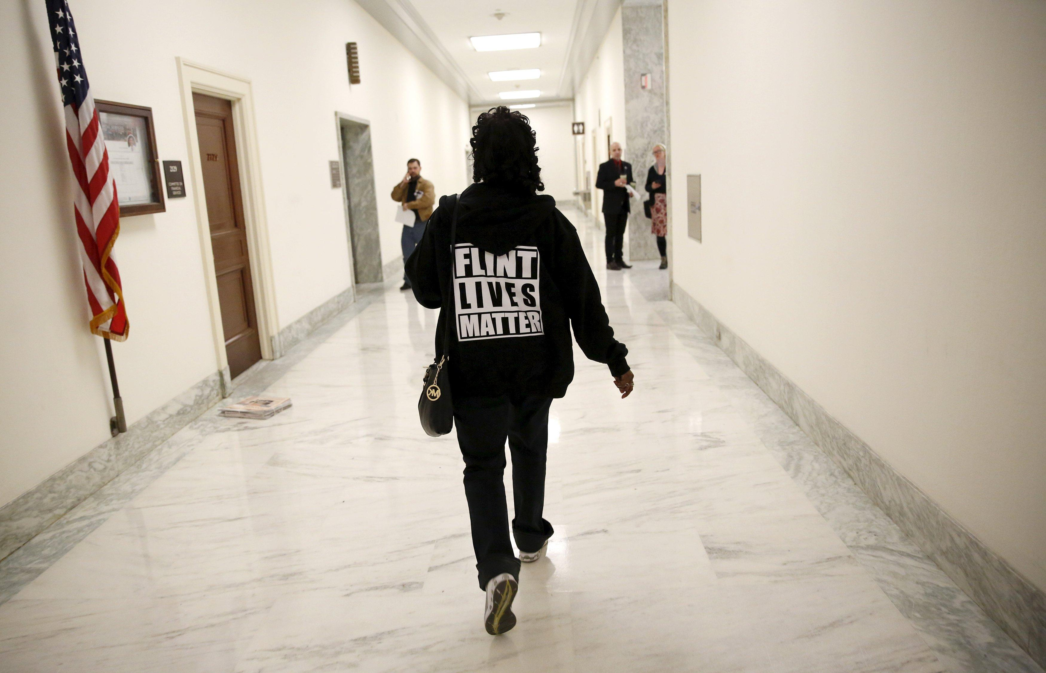 """A woman with a """"Flint Lives Matter"""" shirt walks toward a hearing room where Michigan Governor Rick Snyder and EPA Administrator Gina McCarthy will testify before a House Oversight and government Reform hearing on """"Examining Federal Administration of the Safe Drinking Water Act in Flint, Michigan, Part III"""" on Capitol Hill in Washington March 17, 2016. REUTERS/Kevin Lamarque TPX IMAGES OF THE DAY"""