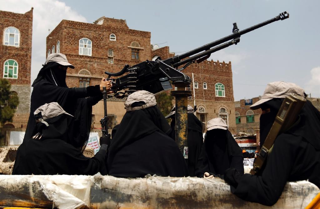 Yemeni female fighters supporting the Shiite Huthi rebels sit in the back of a heavily armed vehicle during an anti-Saudi rally in Sanaa