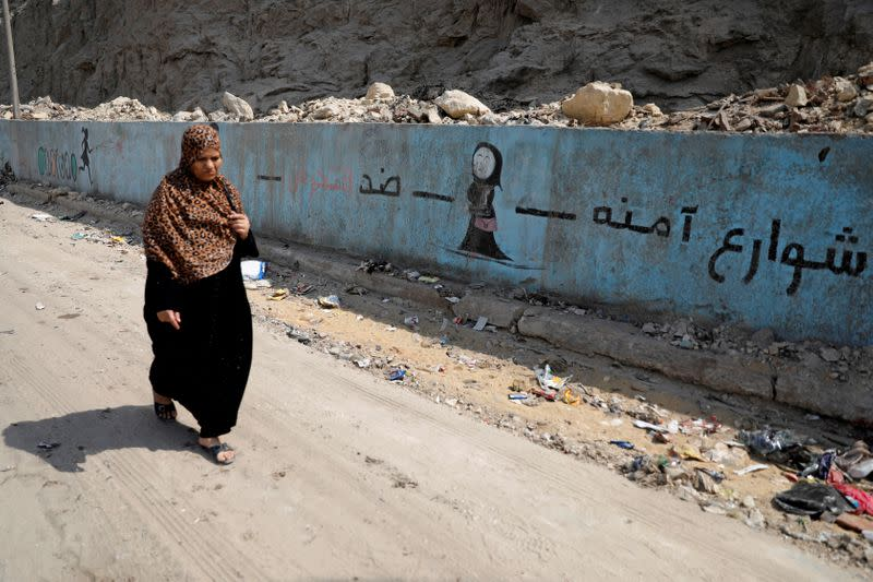 "FILE PHOTO: A woman walks past a mural depicting anti-sexual harassment message and reading ""Safe streets against harassment"" at a highway in Cairo"
