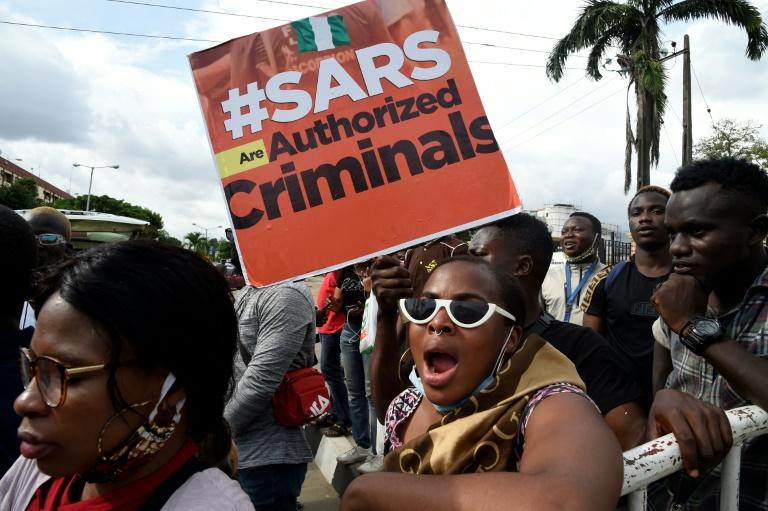 """Protestors carry a placard reading """"Special Anti-Robbery Squad SARS Are Authorised Criminals"""""""