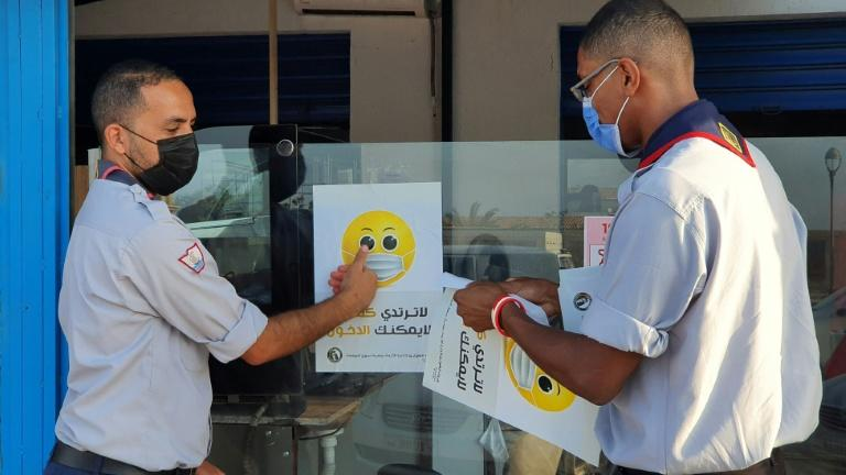 Libyan medical workers stick informative smilies on a shop window for a Covid-19 awareness campaign at the busy Friday market in the capital Tripoli