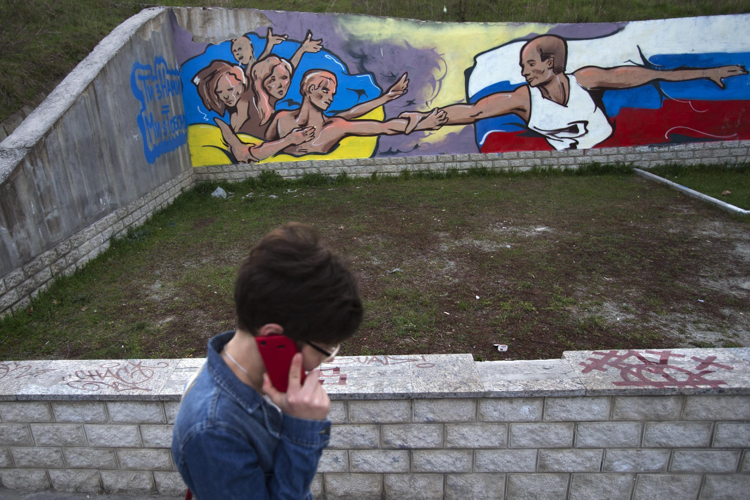 A Ukrainian woman passes by a wall covered with graffiti showing the flags of Ukraine and Russia united in Simferopol, Crimea, Tuesday, March 25, 2014. (AP Photo/Pavel Golovkin)