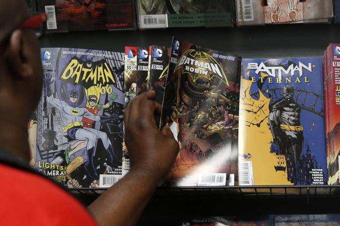 A man reaches for a Batman comic book during Batman Day at the Midtown Comics store in New York July 23, 2014. Comic book stores are celebrating the 75th anniversary of the creation of the Caped Crusader.   REUTERS/Shannon Stapleton (UNITED STATES - Tags: SOCIETY ENTERTAINMENT)