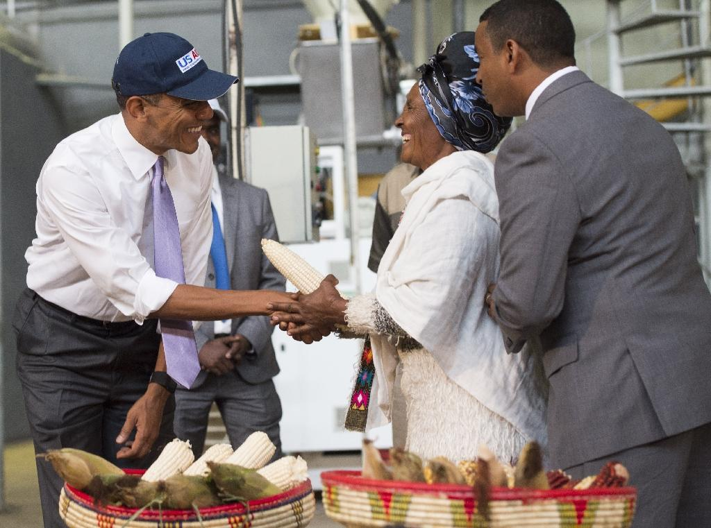 Barack Obama (left) and farmer Gifty Jemal Hussein (centre) talk about improved corn production during a tour of Faffa Food in Addis Ababa on July 28, 2015 (AFP Photo/Saul Loeb)
