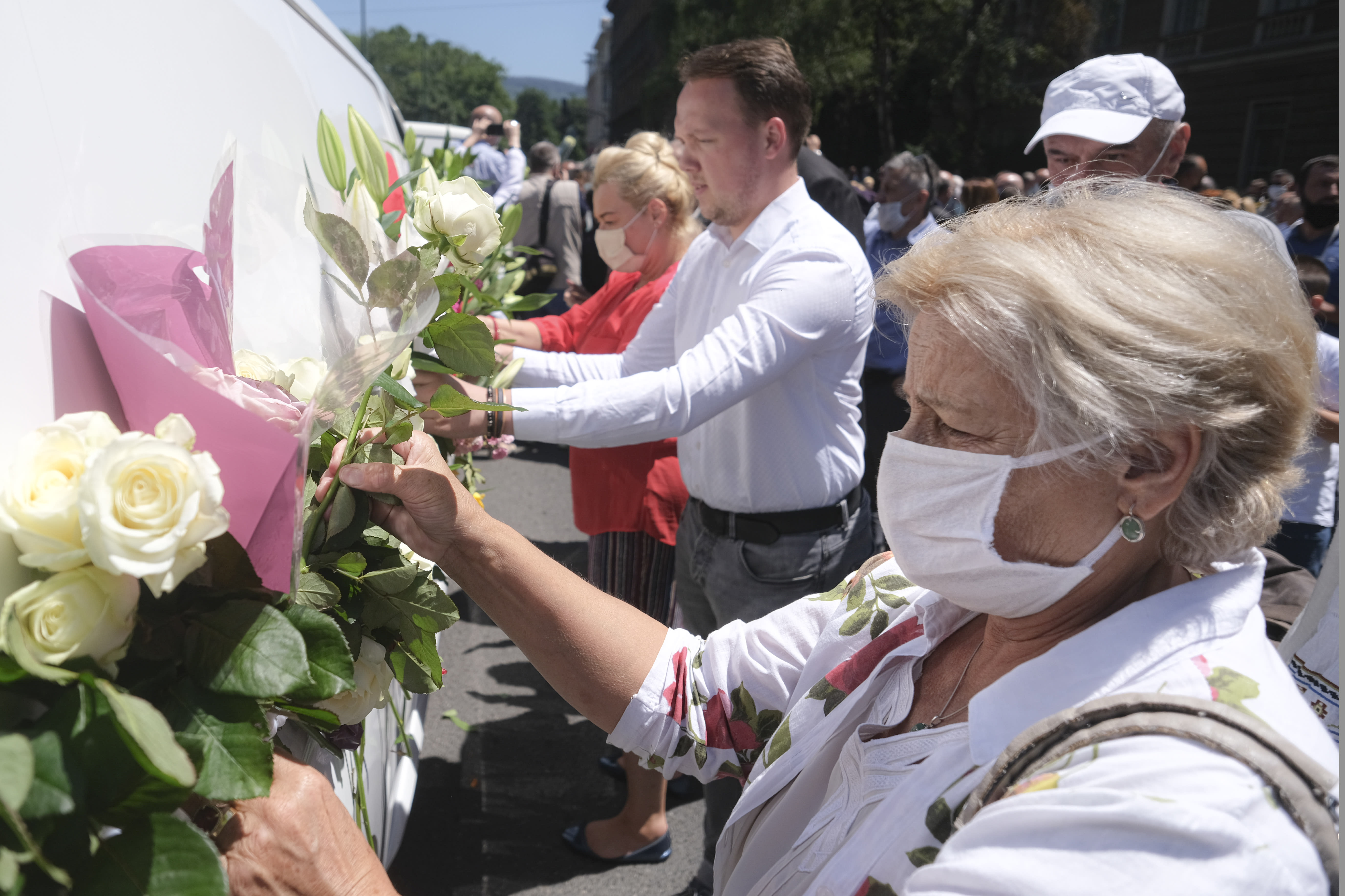 People place flowers on vans as hundreds of people turned out in Sarajevo's main street Thursday, July 9, 2020, to pay respects to eight victims of the Srebrenica massacre as three white vans carried their coffins to a final resting place. The remains of the men and boys, found in mass graves and identified through DNA analysis, will be buried in Srebrenica on Saturday, the 25th anniversary of the massacre, next to 6,610 previously found victims. (AP Photo/Kemal Softic)