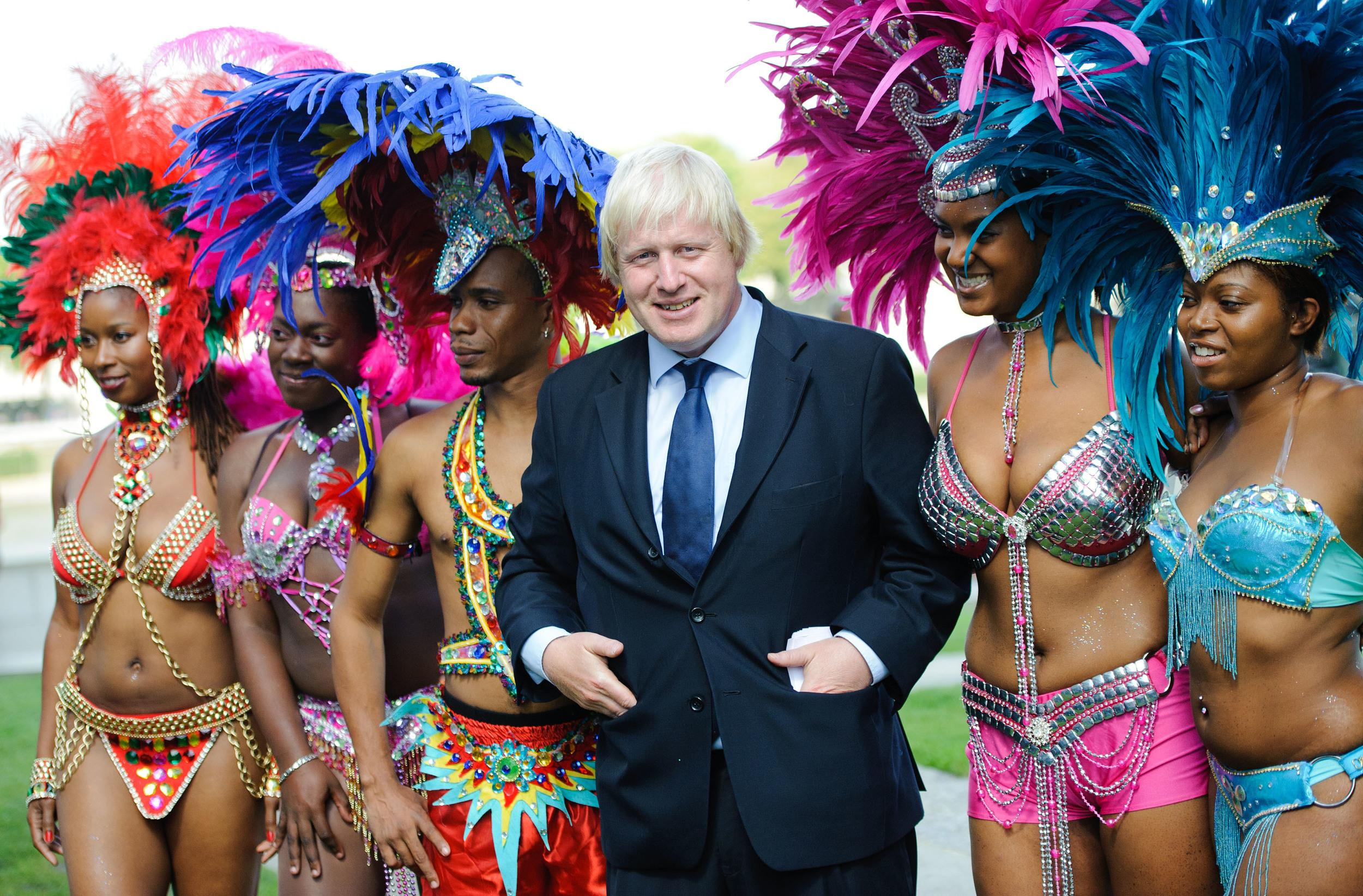 Boris Johnson pictured with members of the Genesis Mas band, who will be performing at the Notting Hill Carnival this weekend, at Potters Fields in central London.