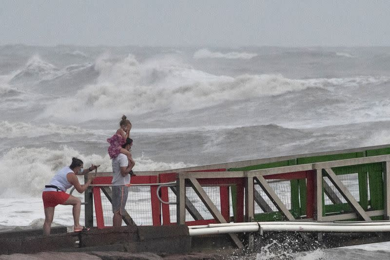 A family watches high swells from Hurricane Hanna from a jetty in Galveston, Texas