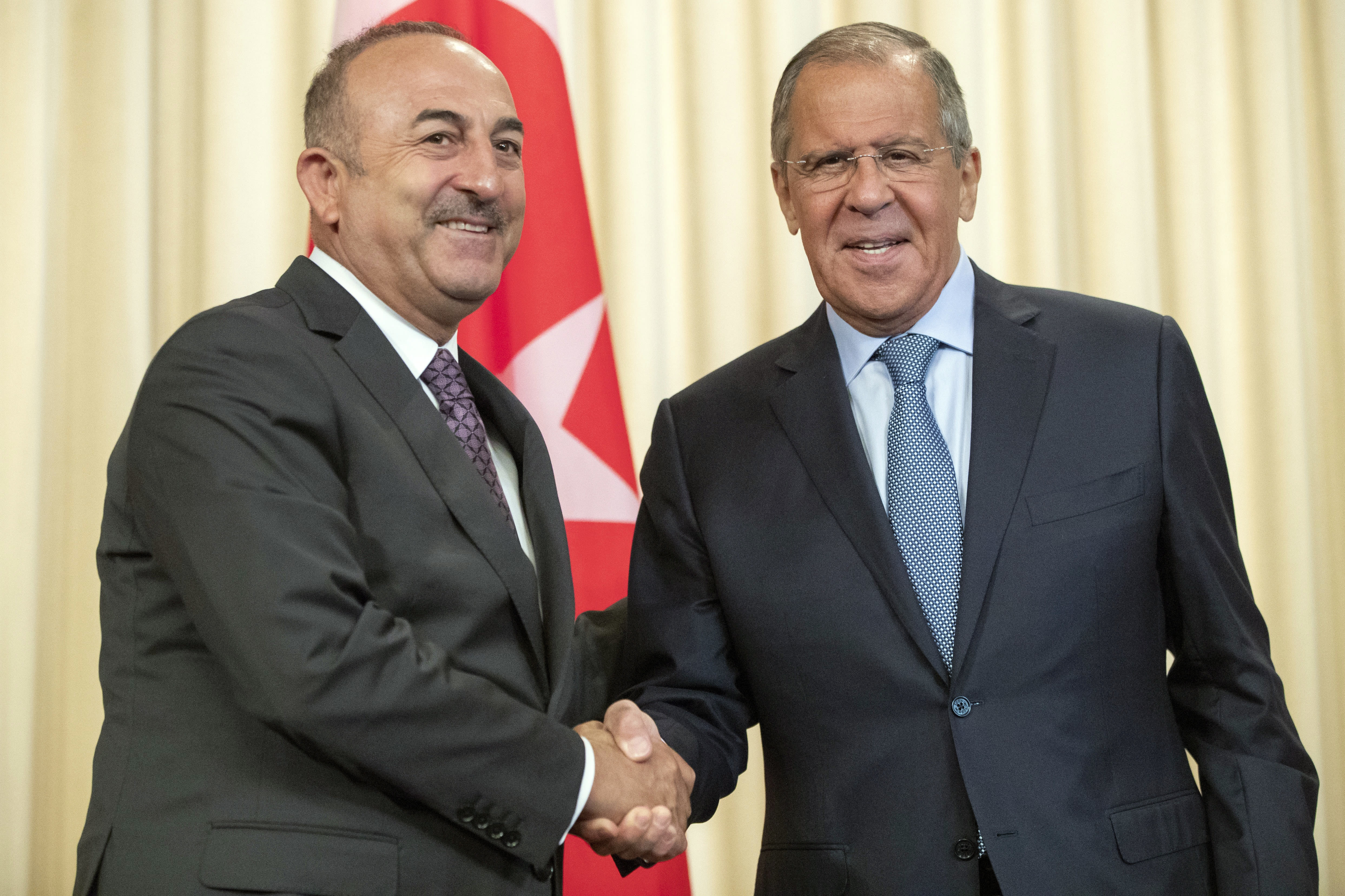 Russian Foreign Minister Sergey Lavrov, right, and his Turkish counterpart Mevlut Cavusoglu shake hands during their meeting in Moscow, Russia, Friday, Aug. 24, 2018. Turkey's Foreign Minister on Friday warned against a possible Syrian government offensive on the last remaining opposition stronghold while Russia indicated that it's losing its patience with the rebels. (AP Photo/Pavel Golovkin)