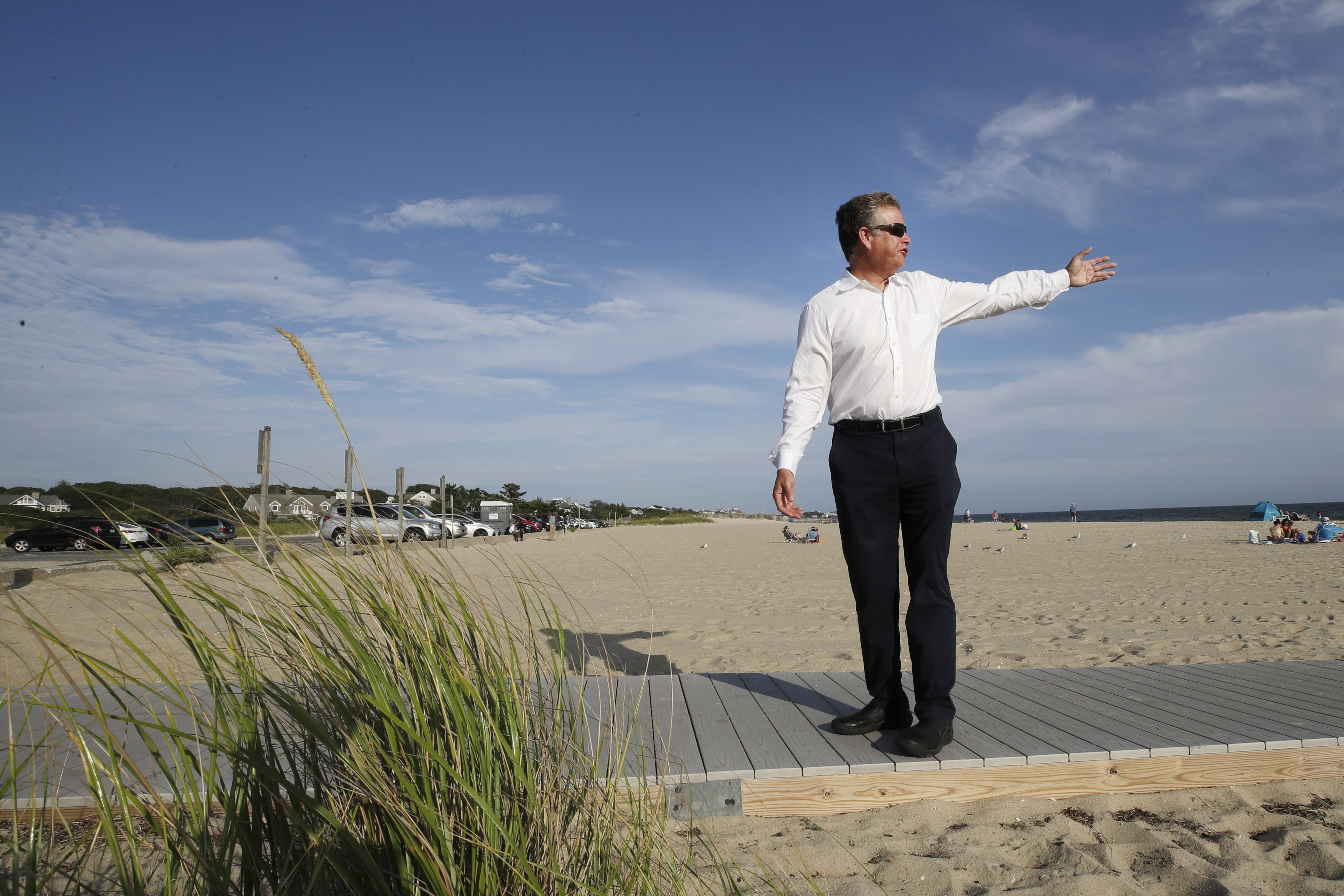 In this Aug. 21, 2019 photo, Andrew Gottlieb, executive director of the Association to Preserve Cape Cod, indicates where the proposed Vineyard Winds' buried energy cables would stretch from offshore wind turbines, through the ocean, under the sand and parking lot at Covell Beach in Centerville, Mass. to a landing point onshore. The cables would then extend to a grid connection point inland. But as Trump has made clear how much he hates wind turbines, all the offshore wind projects, including the nation's first utility-scale offshore wind project, an 84 turbine, $2.8 billion wind farm slated to rise 15 miles off Martha's Vineyard, have stalled. (AP Photo/Elise Amendola)