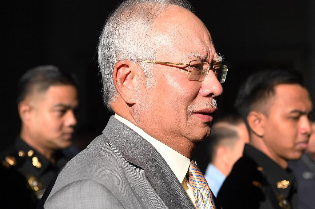 Former Malaysia's prime minister Najib Razak is escorted by police after being charged in Kuala Lumpur