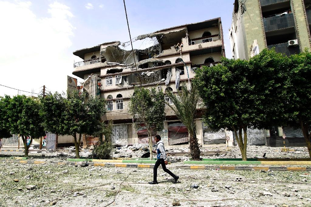 A Yemeni man walks past damaged buildings following an air-strike by the Saudi-led coalition in Sanaa, on September 5, 2015 (AFP Photo/Mohammed Huwais)