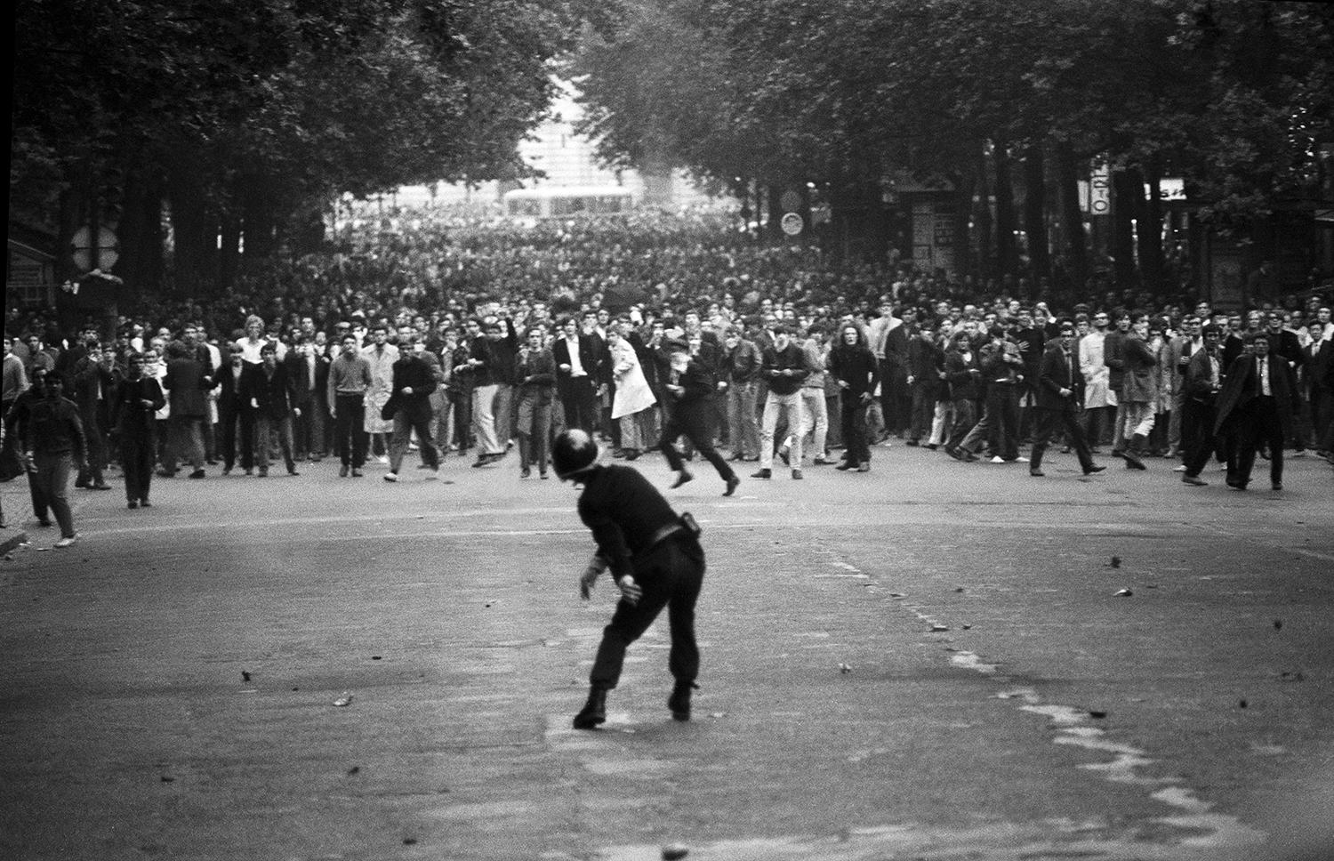 """<p>A police officer confronts defiant students on the Boulevard Saint-Michel during the first day of violent clashes in Paris on May 6, 1968. In all, 1,045 civilians were wounded during what became known as """"the night of the barricades."""" (Photo: Gökşin Sipahioğlu/SIPA) </p>"""