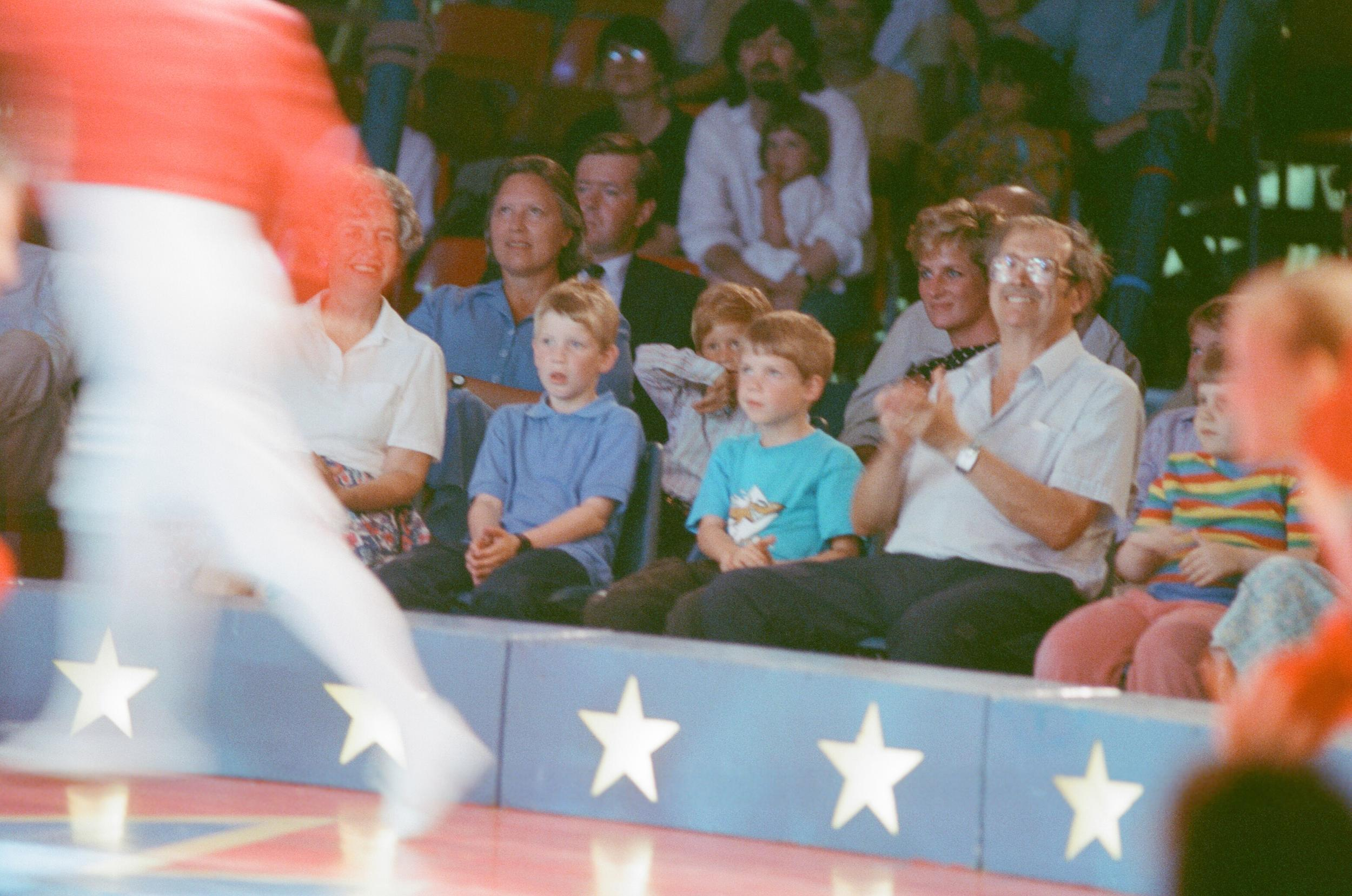 The Princess of Wales, Princess Diana, along with her songs William and Harry enjoy the day at Le Cirque du Soleil, the Children's Circus. Picture shows Diana in the 2nd row, with Prince Harry visible sitting the his mothers right (picture left) Picture taken 8th August 1990. (Photo by Chris Grieve/Mirrorpix/Getty Images)