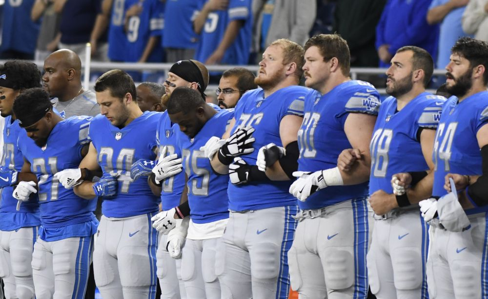 The Lions stand to attention at the playing of the national anthem before Sunday's game against the Panthers in Detroit. (AP)