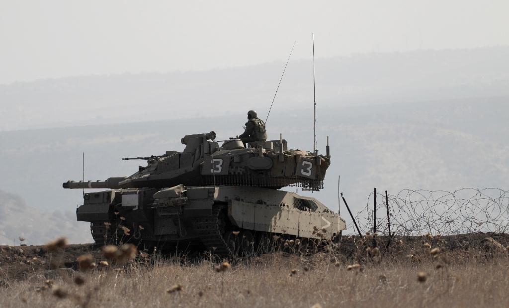Israeli soldiers in a tank monitor the Israel-Syria border in the Israeli-annexed Golan Heights, on November 27, 2016 (AFP Photo/Jalaa Marey)