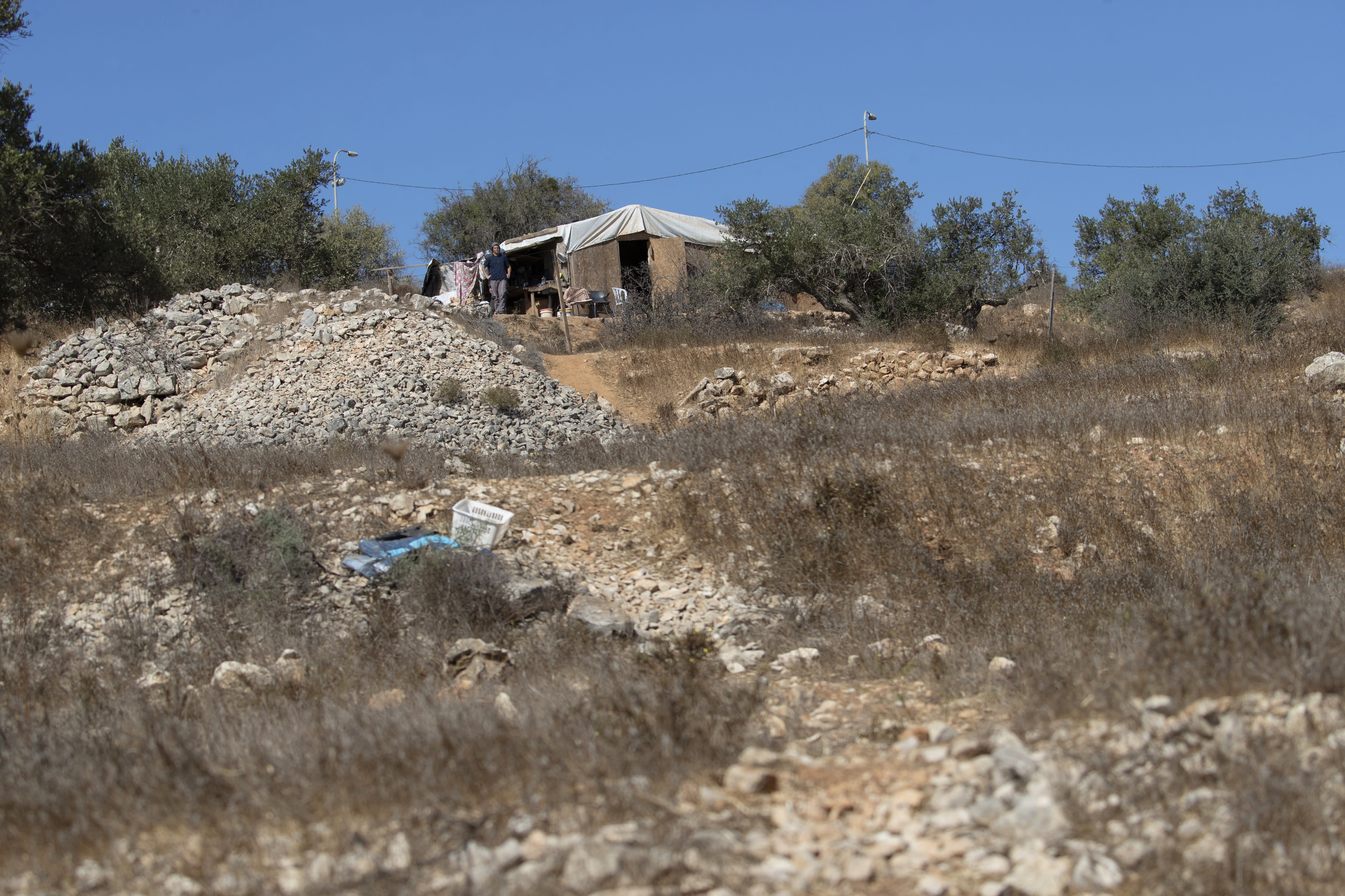 A Jewish settler watches from the settlers outpost that overlooks Palestinian olive groves, in the West Bank village of Burqa, East of Ramallah, Friday, Oct. 16, 2020. Palestinians clashed with Israeli border police in the West Bank on Friday during their attempt to reach and harvest their olive groves near a Jewish settlers outpost. (AP Photo/Nasser Nasser)
