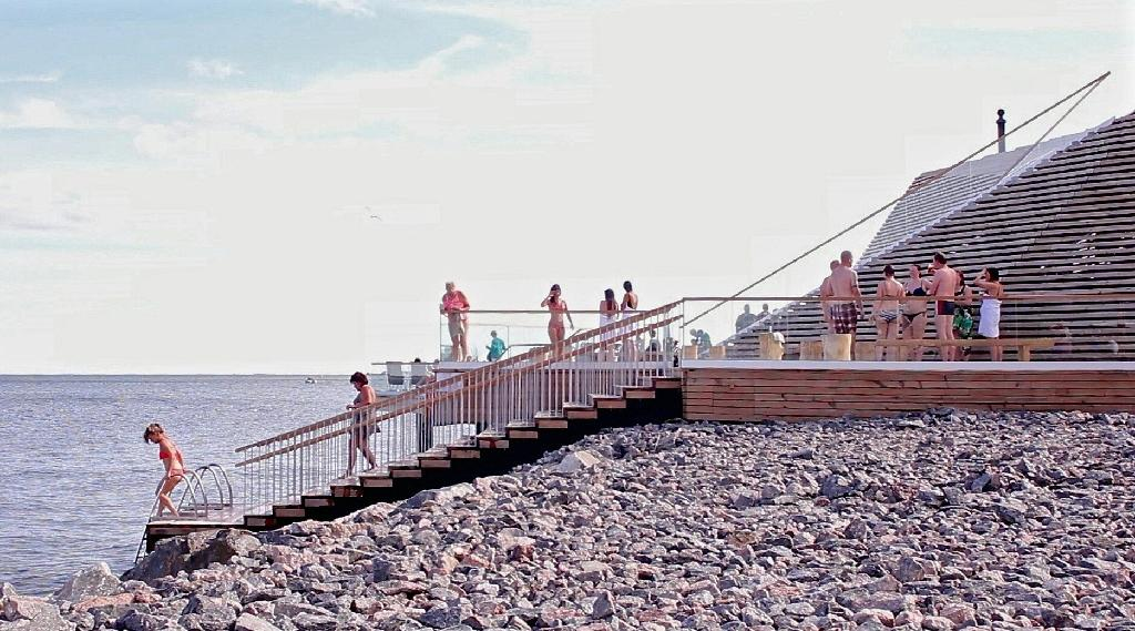 """Sauna-goers dip in the Baltic Sea at a new boutique sauna called Loyly (Finnish for """"Steam"""") in Helsinki on July 7, 2016 (AFP Photo/Sam Kingsley)"""