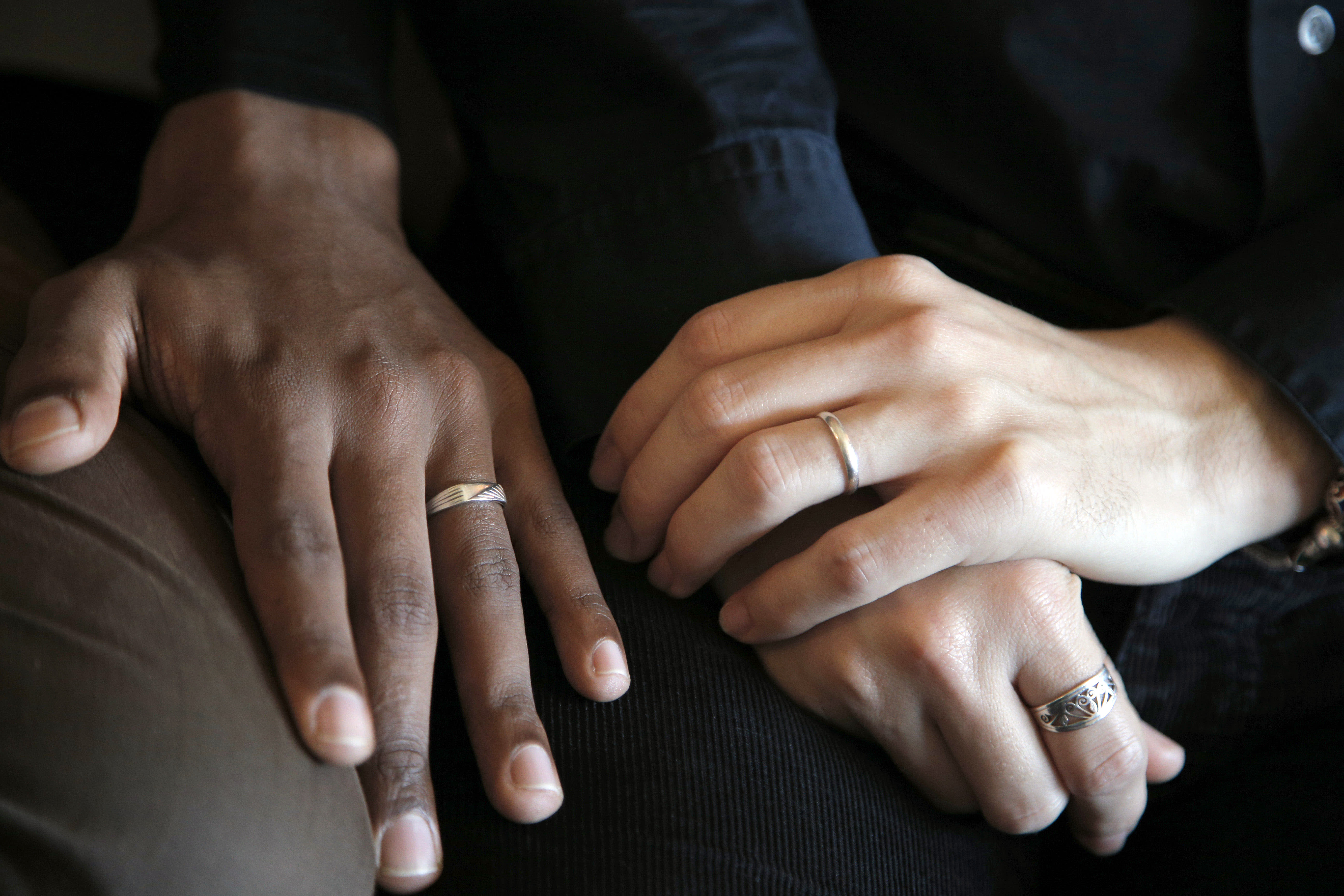 """In this photo taken on Monday, Oct. 22, 2012, the hands of Ludovic-Mohamed Zahed, right, who married his live-in partner Qiyaammudeen Jantjies, left, in South Africa, where gay marriage is recognized, during an interview with the Associated Press in Sevran, outside Paris. A plan to legalize same-sex marriage and allow gay couples to adopt was a liberal cornerstone of French President Francois Hollande's election manifesto earlier this year. It looked like a shoo-in, supported by a majority of the French, and an easy way to break with his conservative predecessor. But that was then, Now, as the Socialist government prepares to unveil its draft """"marriage for everyone"""" law Wednesday, polls show wavering support for the idea and for the president amid increasingly vocal opposition in this traditionally Catholic country. Ludovic-Mohamed Zahed, who married his live-in partner Qiyaammudeen Jantjies in South Africa, where gay marriage is recognized, is already seeking instruction from his local town council to get his marriage recognized in France as soon as he can. (AP Photo/Christophe Ena)"""
