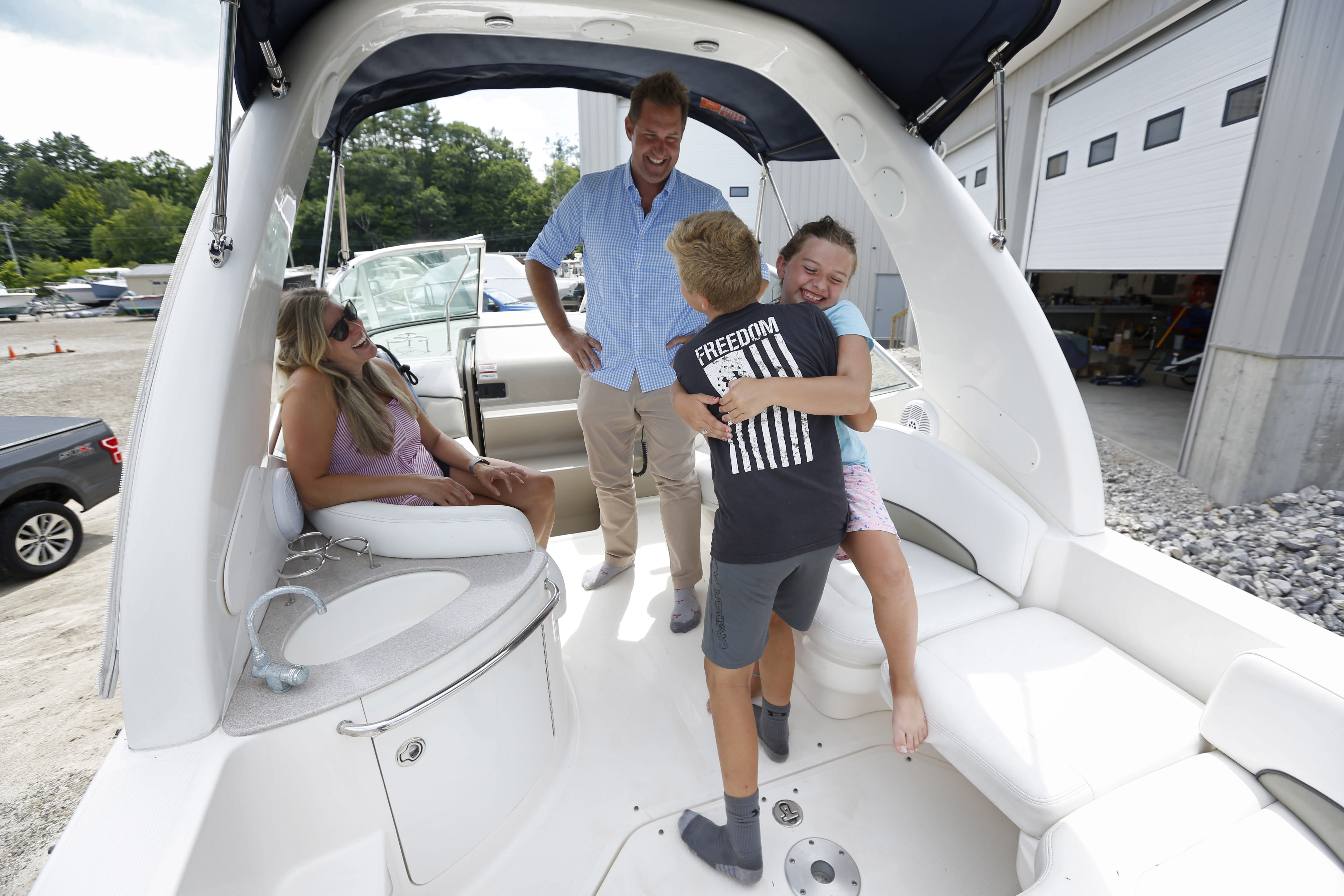 Carter Mitchell hugs his sister, Emerson, moments after climbing aboard the family's new boat, Friday, July 24, 2020, in Yarmouth, Maine. Brandon and Hilary Mitchell, of Cape Elizabeth, Maine, surprised their children with the new purchase after the coronavirus pandemic forced them to cancel summer travel plans. (AP Photo/Robert F. Bukaty)