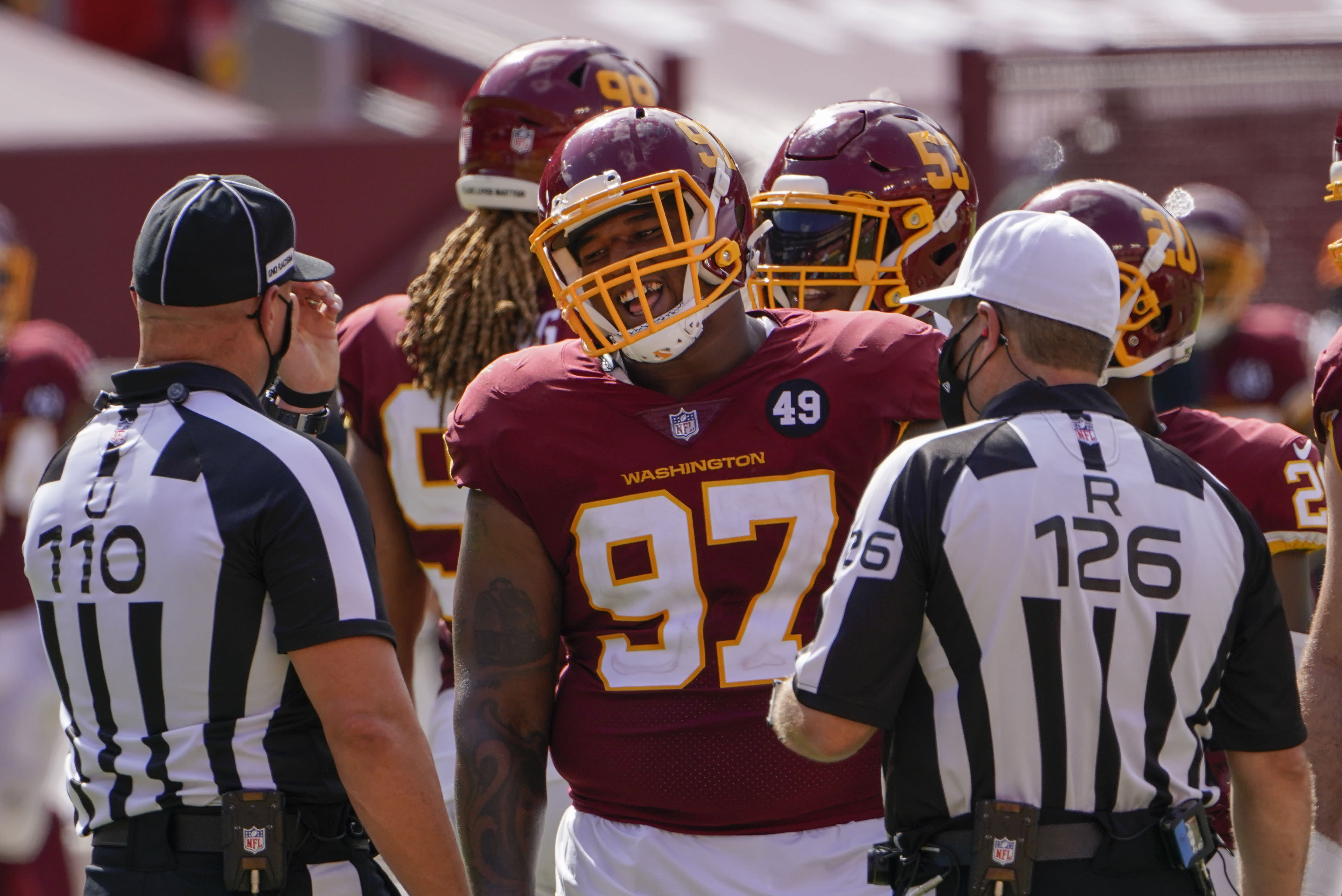 Washington Football Team defensive tackle Tim Settle (97) smiles while talking with umpire Tab Slaughter (110) and referee Brad Rodgers (126) during a timeout in the second half of an NFL football game against the Philadelphia Eagles, Sunday, Sept. 13, 2020, in Landover, Md. (AP Photo/Susan Walsh)