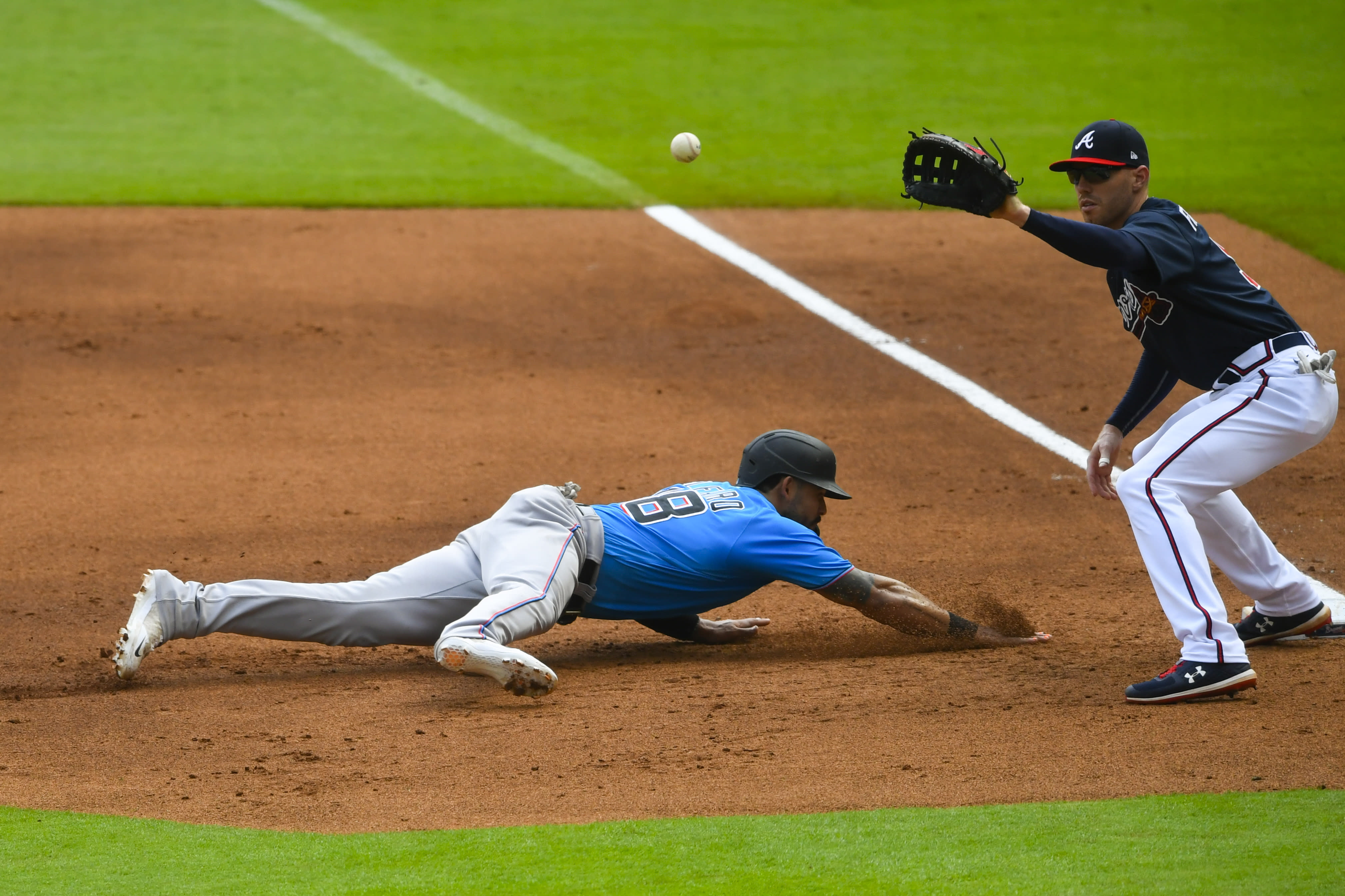 Miami Marlins' Jorge Alfaro beats a pick off attempt as Atlanta Braves' Freddie Freeman covers first base during the first inning of an exhibition baseball game Wednesday, July 22, 2020, in Atlanta. (AP Photo/John Amis)