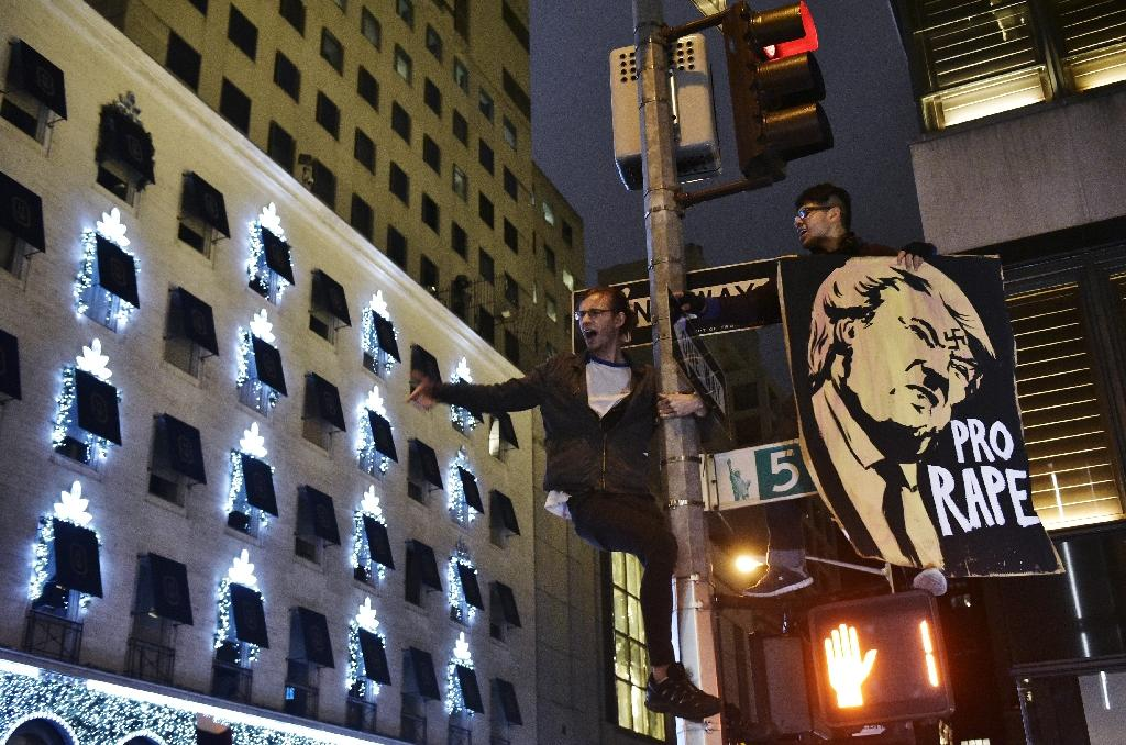 Protestors shout slogans from a lampost during a demonstration across from Trump Tower in New York (AFP Photo/Mandel Ngan)
