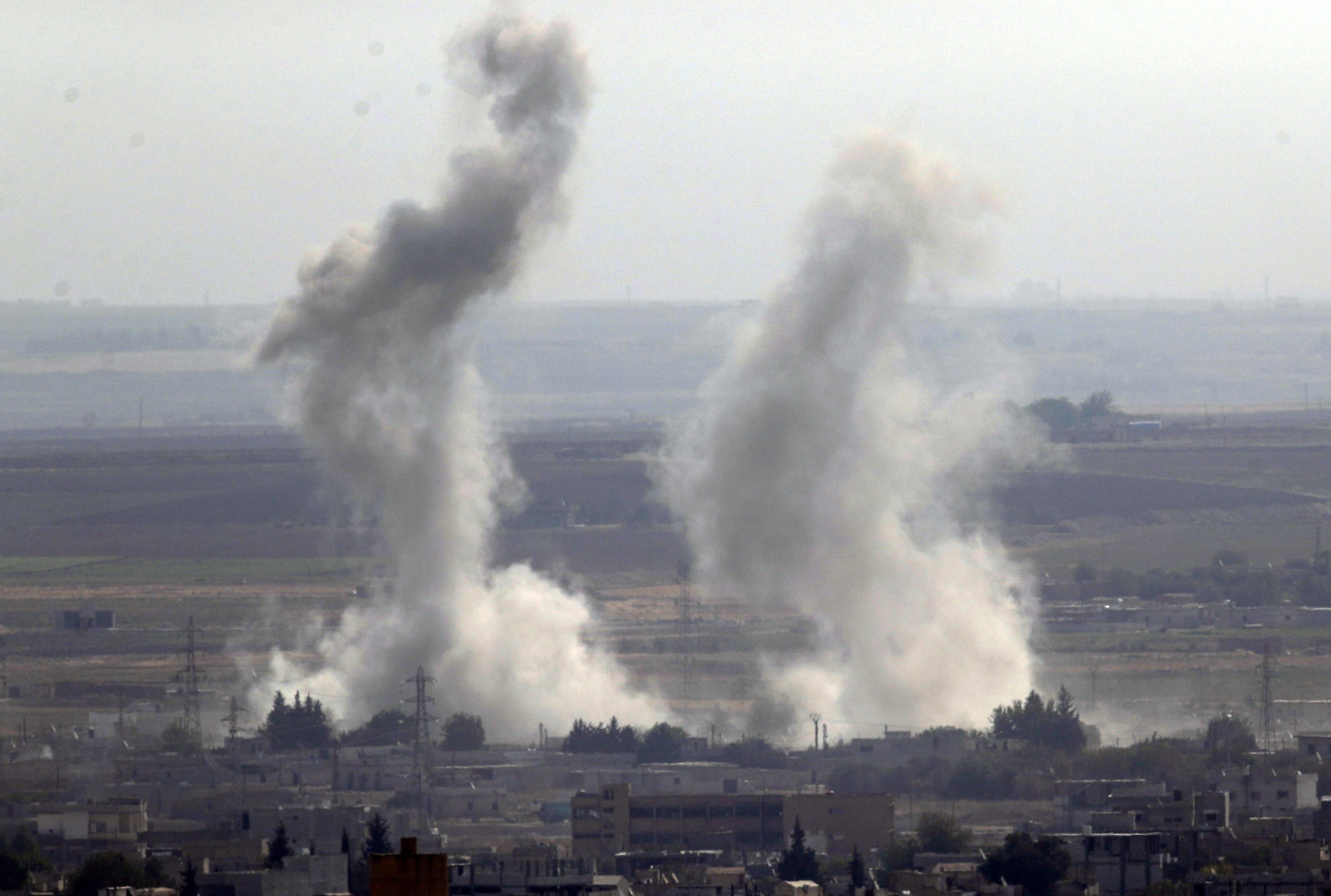 In this photo taken from the Turkish side of the border between Turkey and Syria, in Ceylanpinar, Sanliurfa province, southeastern Turkey, smoke and dust billows from targets in Ras al-Ayn, Syria, caused by bombardment by Turkish forces, Tuesday, Oct. 15, 2019. Turkish artillery on Tuesday pounded suspected Syrian Kurdish positions near the town in northeast Syria amid reports that Kurdish fighters had retaken the town as Turkey pressed ahead with a military incursion that has drawn widespread condemnation. (AP Photo/Cavit Ozgul)