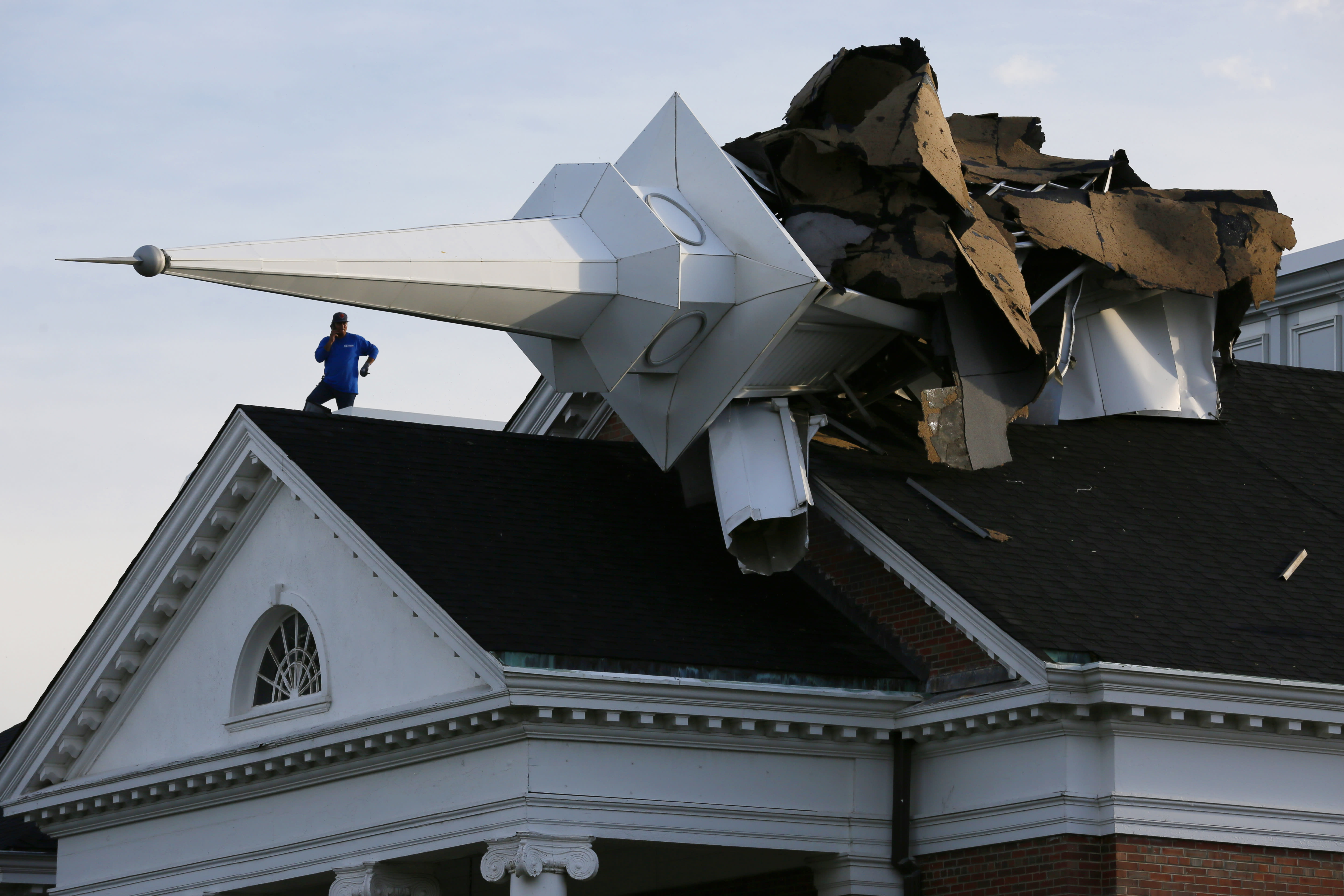 A person surveys the damage from the roof of College Church in Wheaton, Ill., after a severe storm toppled the church steeple on the campus of Wheaton College, Monday, Aug. 10, 2020. (Mark Hume/Chicago Tribune via AP)