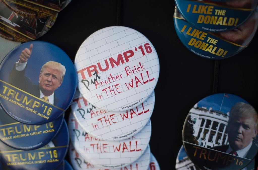 Buttons referring to Republican Presidential candidate Donald Trump's immigration policies for sale outside a Trump Rally in Marshalltown, Iowa, January 26, 2016, ahead of the Iowa Caucus (AFP Photo/Jim Watson)