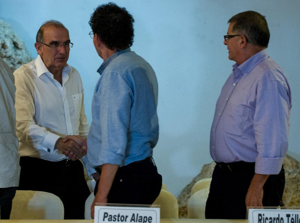 FARC commander Pastor Alape (C) and head of the Colombian delegation for peace talks Humberto de la Calle (L) shake hands during a press conference in Havana, on October 17, 2015