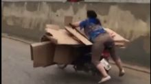 Woman filmed balancing on top of cardboard boxes as she rides her motorbike along a busy Chinese road