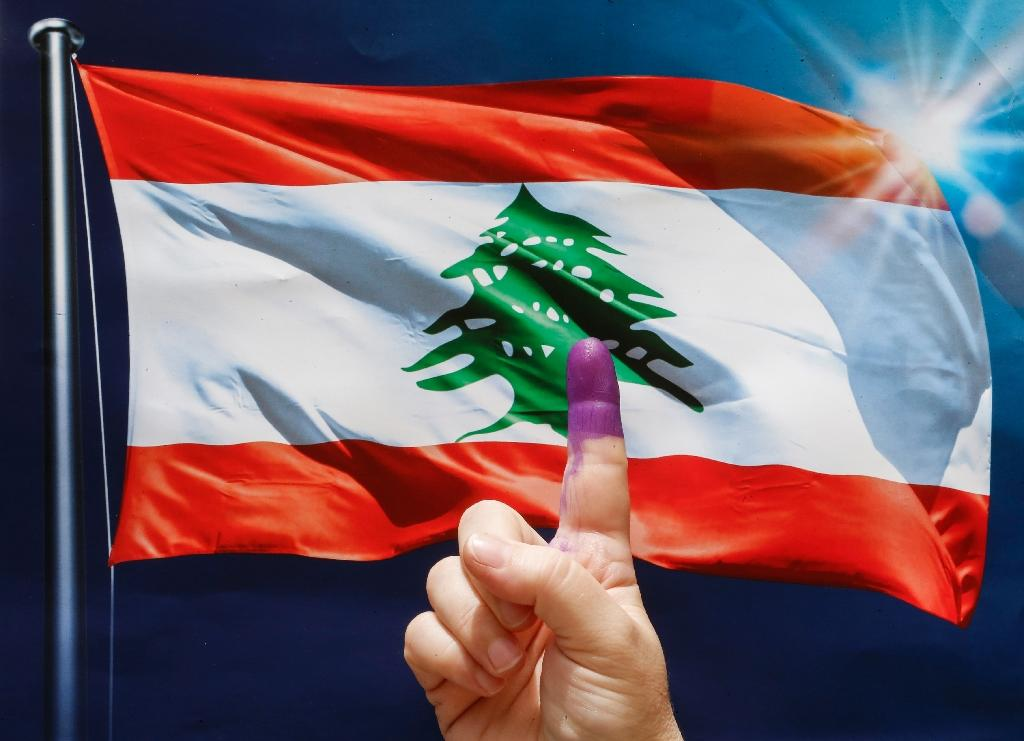 A woman flashes her ink-stained index finger in front of a Lebanese flag after voting in Lebanon's first parliamentary elections in nine years in the capital Beirut on May 6, 2018 (AFP Photo/ANWAR AMRO)