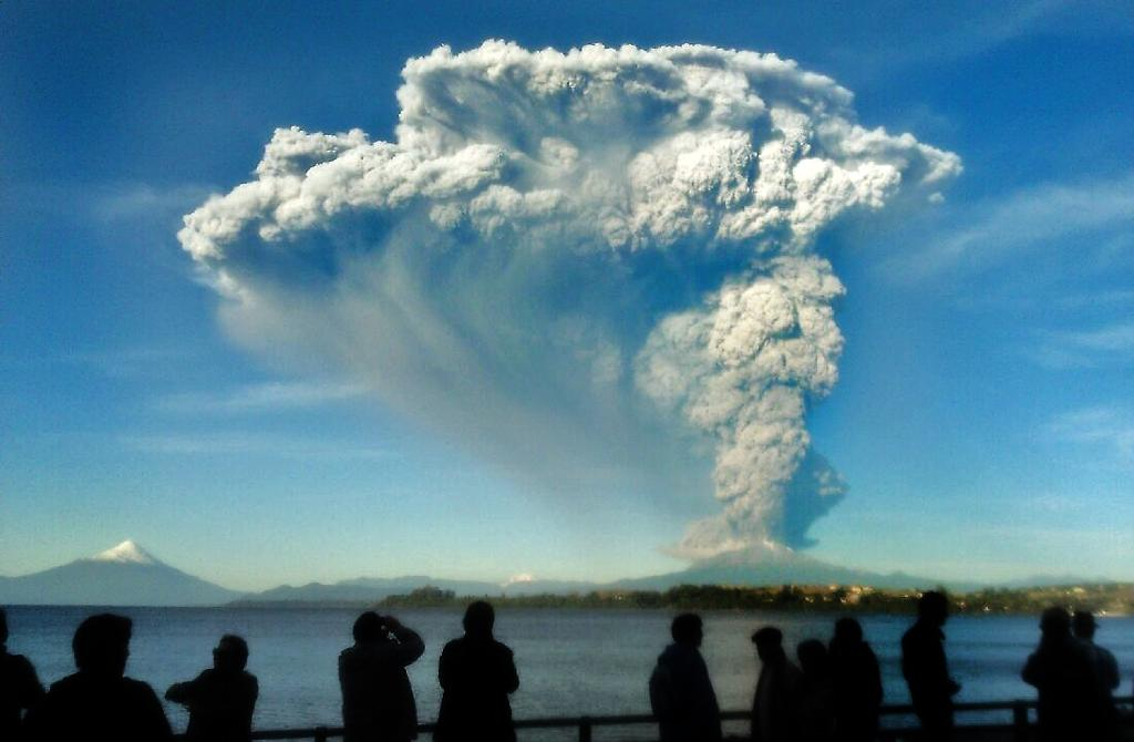 People watch from Puerto Varas, southern Chile, as a high column of ash and lava spews from the Calbuco volcano, on April 22, 2015 (AFP Photo/Giordana Schmidt)