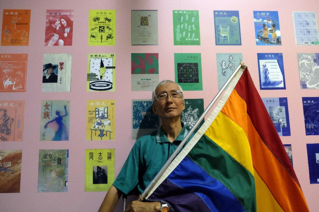 This picture taken on May 19, 2017 shows Taiwanese gay rights campaigner Chi Chia-wei, 59, posing for a photograph with a flag during an exhibition in Taipei (AFP Photo/SAM YEH)