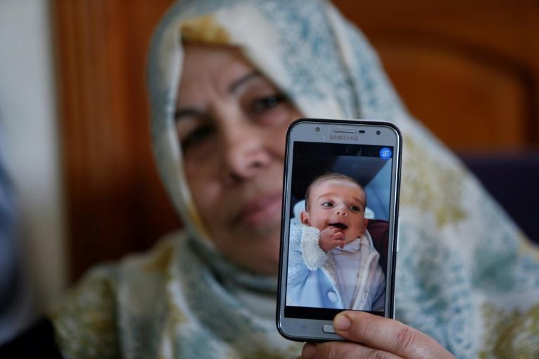 The grandmother of Palestinian baby Omar Yagi displays a picture of him taken before his death in Gaza last week from a serious heart condition he had been due to receive life-saving surgery in Israel for