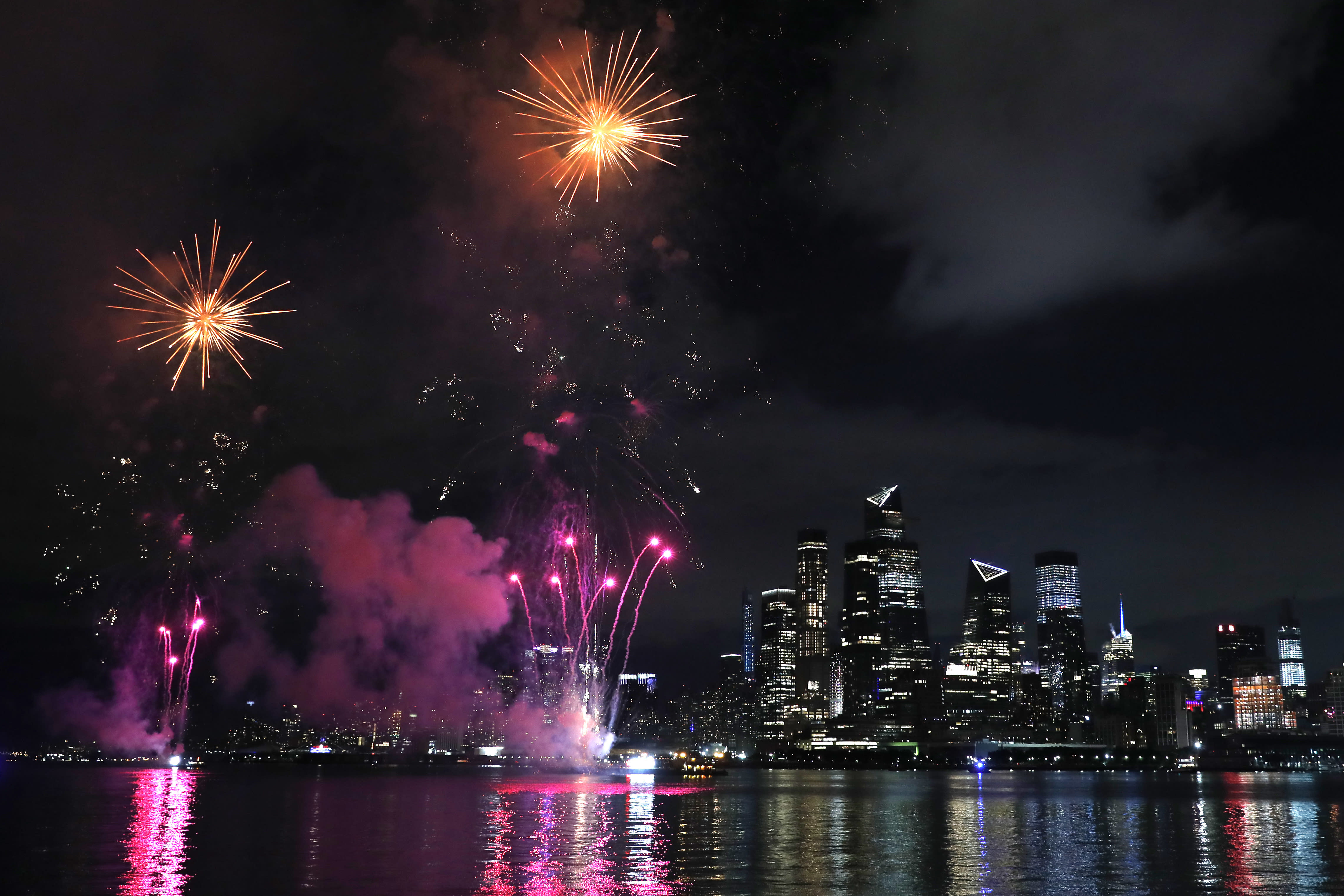 A surprise display of fireworks sponsored by Macy's explode over the Hudson Yards area of Manhattan as seen from a pier in Hoboken, N.J., late Tuesday, June 30, 2020. The fireworks were not announced until an hour or so before to avoid attracting large crowds. (AP Photo/Kathy Willens)