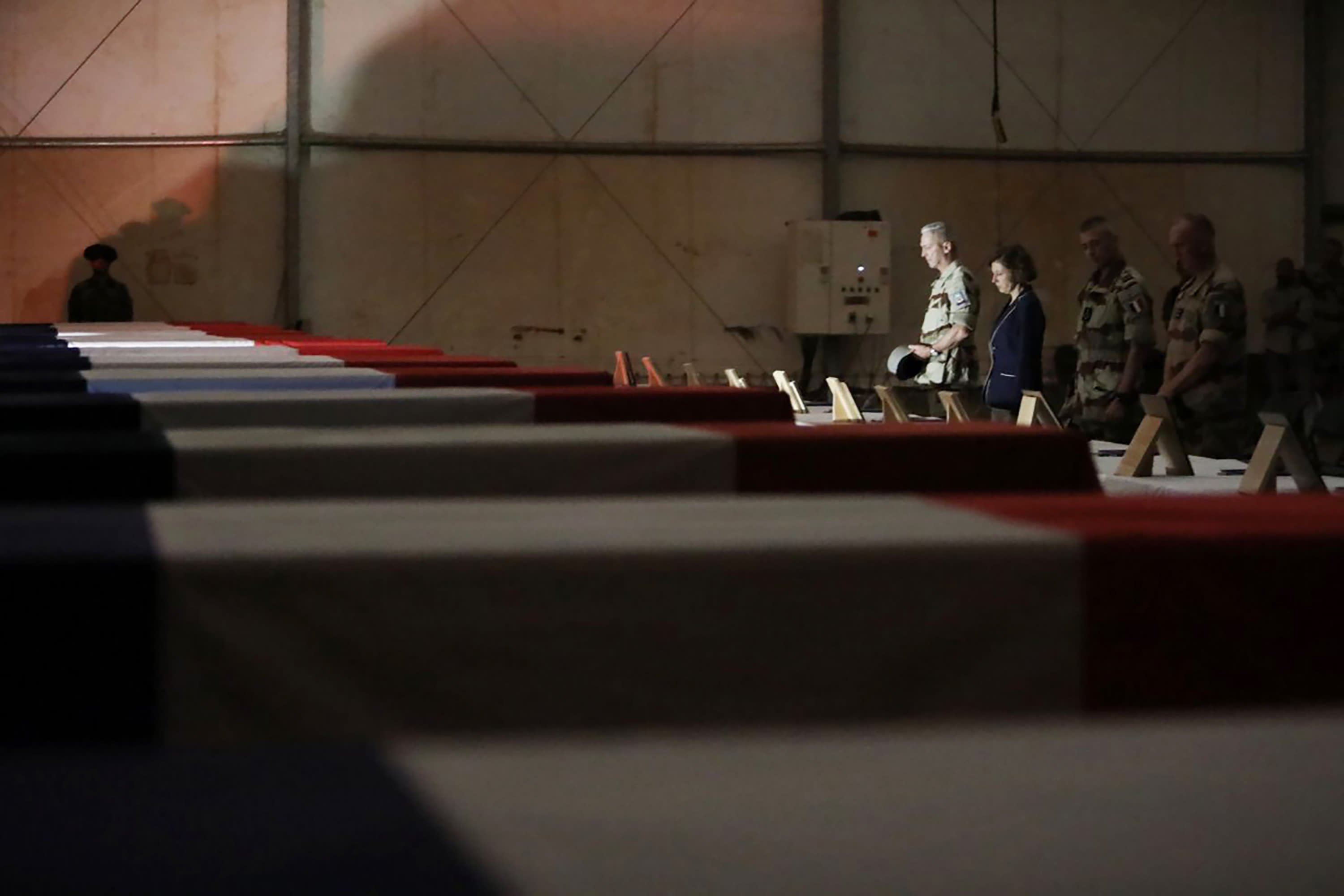 In this Wednesday, Nov. 27, 2019, photo provided by French Defense Communication and Audiovisual Department (ECPAD), French Defense Minister Florence Parly, third right, and French Army Chief of Staff Gen. Francois Lecointre pay their respects to the 13 French soldiers, in Gao, Mali. Parly arrived in northern Mali on Wednesday after a helicopter collision killed 13 French soldiers fighting Islamic State group-linked extremists, while some in the West African country debated France's military presence. (Veronique Besnard/ECPAD via AP)