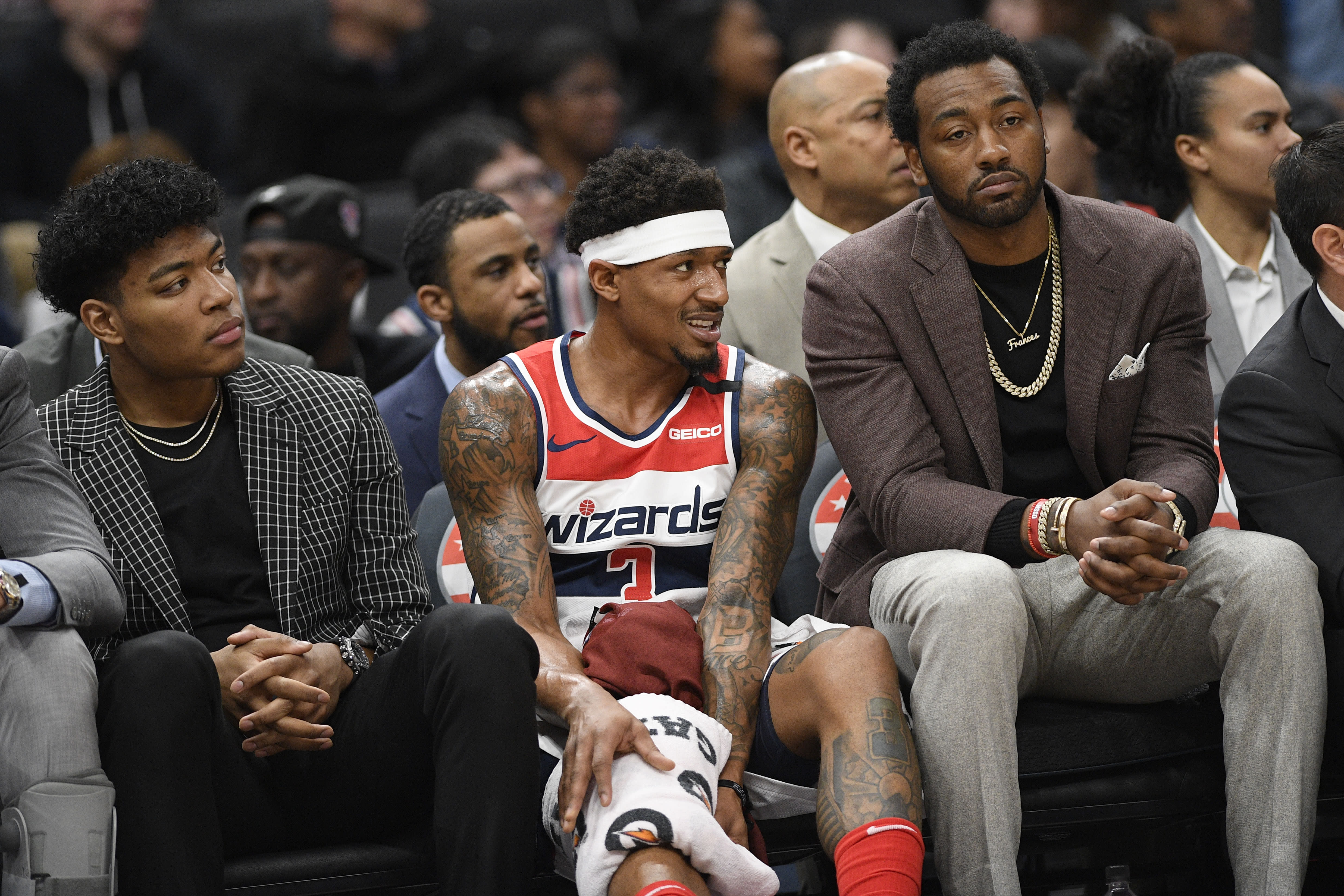 Washington Wizards forward Rui Hachimura, left, of Japan, guard Bradley Beal, center, and guard John Wall, right, watch from the bench during the first half of an NBA basketball game against the Utah Jazz, Sunday, Jan. 12, 2020, in Washington. (AP Photo/Nick Wass)