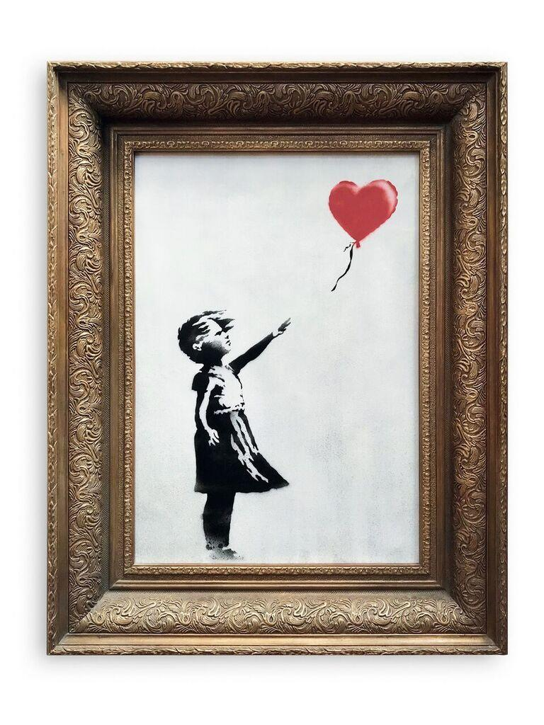 "A pre-sale photo supplied by Sotheby's in London on October 6, 2018 shows ""Girl with Balloon"" by the British artist Banksy, which sold on October 5 for £1,042,000 and then unexpectedly passed through a shredder hidden in the frame"