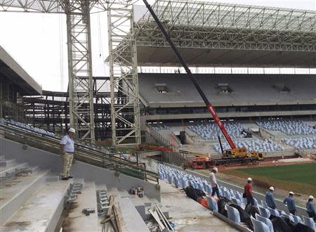 An official from Brazil's World Cup organizers accompanies visitors on a tour inside the Arena Pantanal soccer stadium in Cuiaba