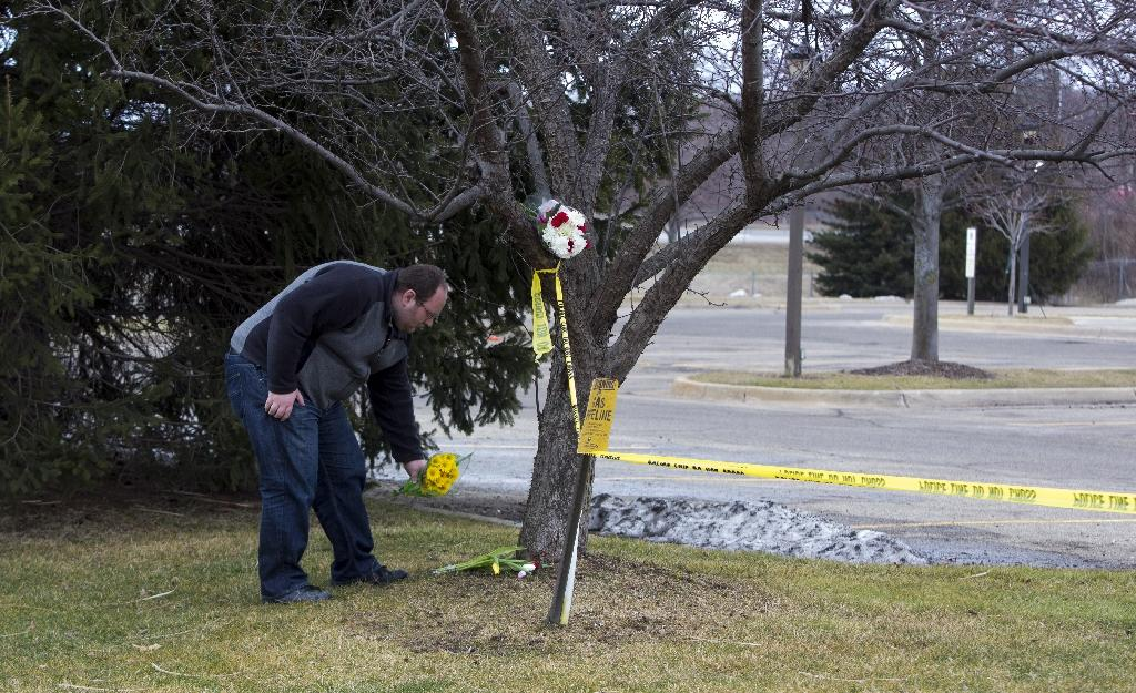 A man places flowers outside a Cracker Barrel where a gunman went on a shooting rampage, on February 21, 2016 in Kalamazoo, Michigan (AFP Photo/Tasos Katopodis)