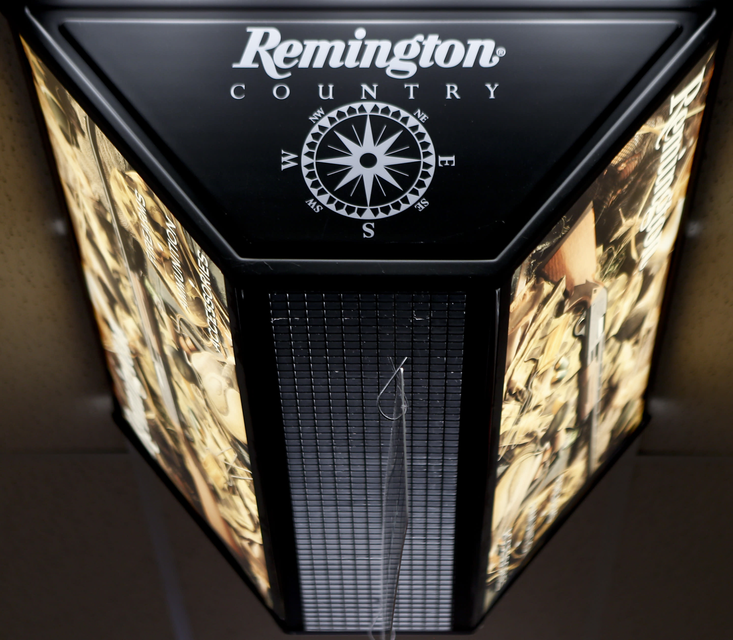 FILE - In this March 1, 2018 file photo, a light advertising Remington products hangs from the ceiling at Duke's Sport Shop in New Castle, Pa. For years, the gun industry has been immune from most lawsuits, but a recent ruling allowing families of victims in the Newton school shooting to challenge the way an AR-15 used by the shooter was marketed is upending that longstanding roadblock. The U.S. Supreme Court recently rejected efforts by gunmaker Remington to quash the lawsuit, allowing it to continue to be heard in Connecticut courts.(AP Photo/Keith Srakocic, File)