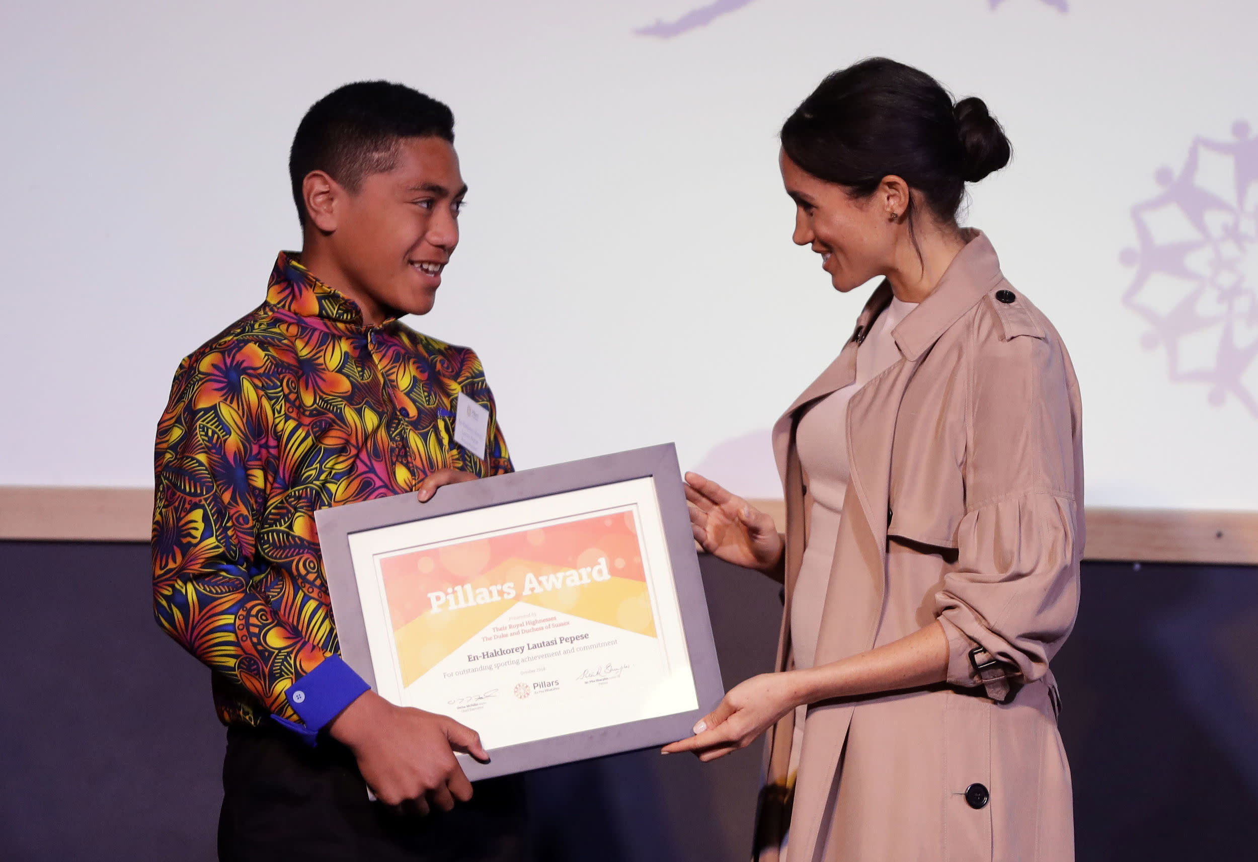 The Duchess of Sussex presents an award to En-Hakkorey Lautasi Pepese during a visit to Pillars, in Auckland, New Zealand, which is a charity operating across New Zealand that supports children who have a parent in prison by providing special mentoring schemes, on day three of the royal couple's tour of New Zealand.