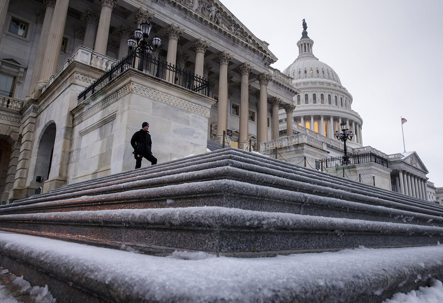 <p>A police officer stands at his post on the steps of the House of Representatives on Capitol Hill in Washington, Tuesday morning, March, 14, 2017, following an overnight snowfall. A late-season storm is dumping a messy mix of snow, sleet and rain on the mid-Atlantic, complicating travel, knocking out power and closing schools and government offices around the region. (J. Scott Applewhite/AP) </p>