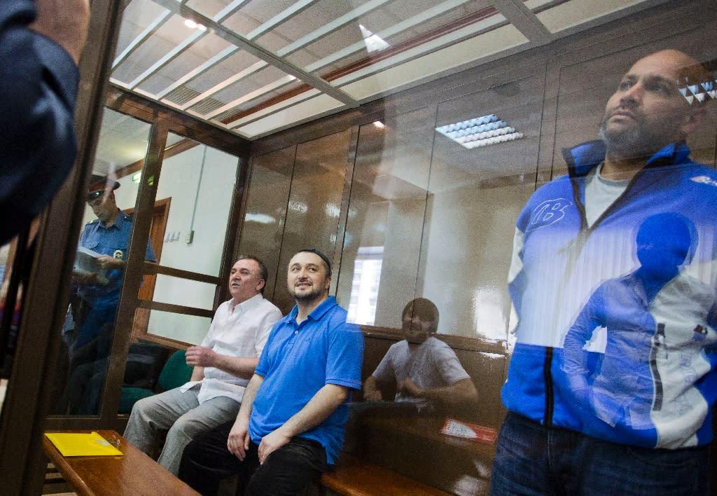 Rustam Makhmudov (2nd L), Lom-Ali Gaitukayev and former Moscow police officer Sergei Khadzhikurbanov (R) on trial for the murder of Anna Politkovskaya in Moscow's City Court in 2013 (AFP Photo/Evgeny Feldman)