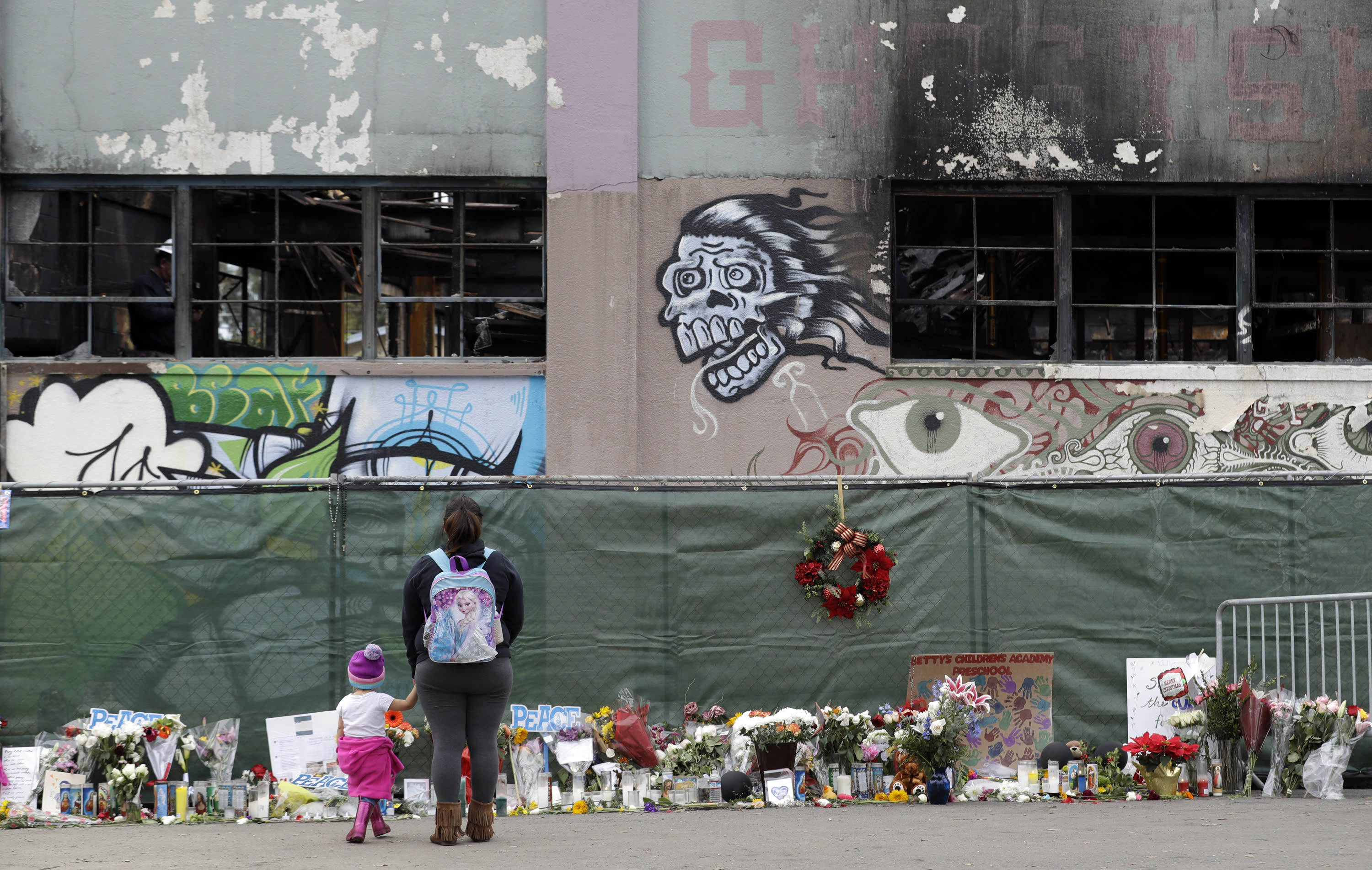 FILE - In this Dec. 13, 2016, file photo, flowers, pictures, signs and candles, are placed at the scene of a warehouse fire in Oakland, Calif. A judge will hear a motion asking the court to uphold a plea bargain that was reached with two men accused of being responsible for a warehouse fire that killed two dozen people at an unlicensed party. (AP Photo/Marcio Jose Sanchez, File)
